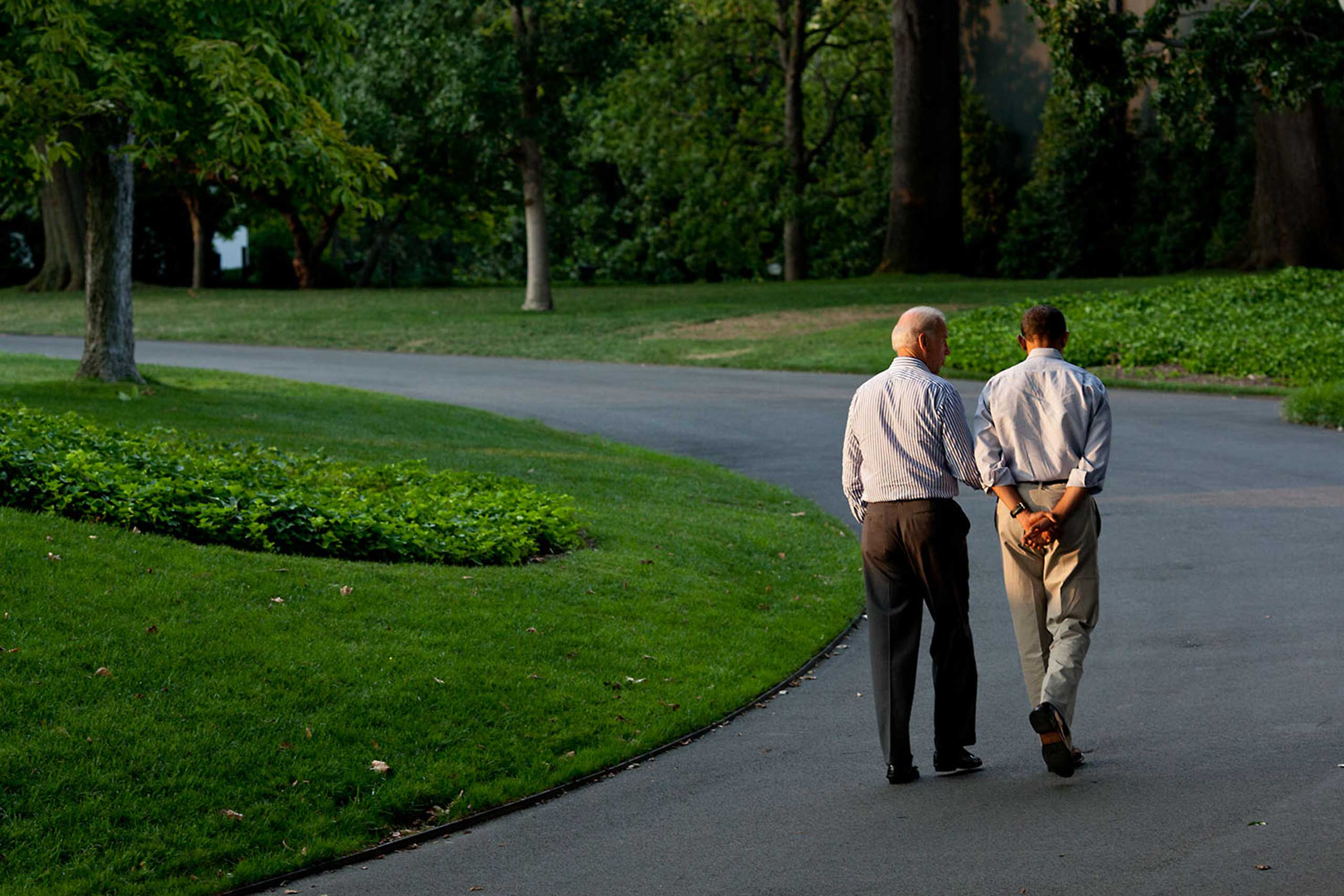 During a break in the debt limit and deficit negotiations with Congressional leaders, the President walks around the South Lawn drive of the White House with the Vice President on Sunday, July 24, 2011. As they walked, I was trying to catch them where there was one pocket of sunlight seeping through the trees.