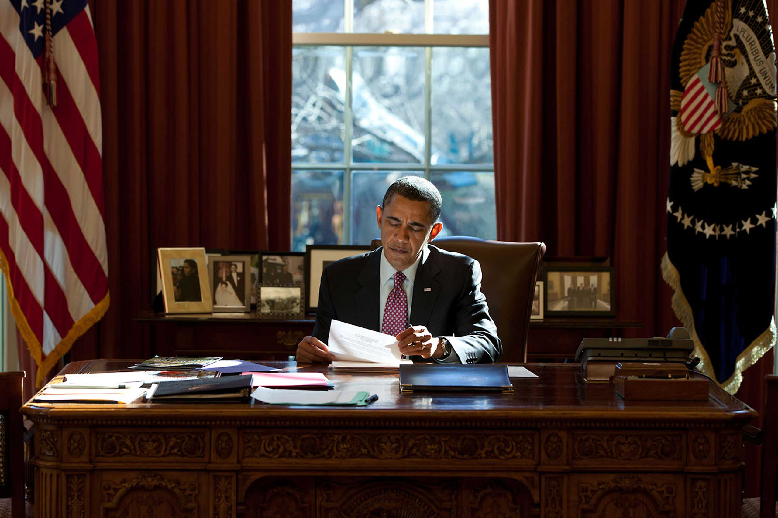 President Obama reads documents while sitting at the Resolute Desk in the Oval Office, Feb. 11, 2011.