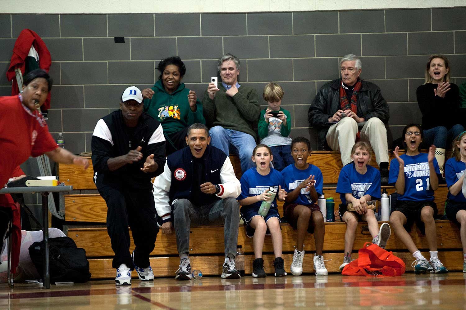 The two coaches for Sasha Obama's basketball team couldn't make it to one of her games, so the President and his then personal aide, Reggie Love, filled in as coaches for this game on Saturday, Feb. 5, 2011. Here they along with Sasha's teammates react during the game.