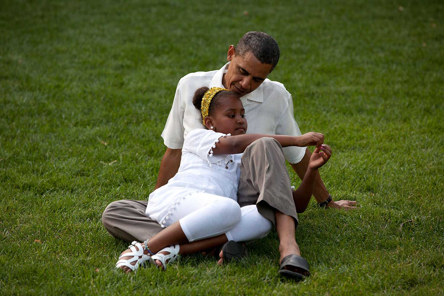 President Obama shares a moment with his daughter Sasha during a barbecue in celebration of his 49th birthday on the South Lawn of the White House, Aug. 8, 2010.