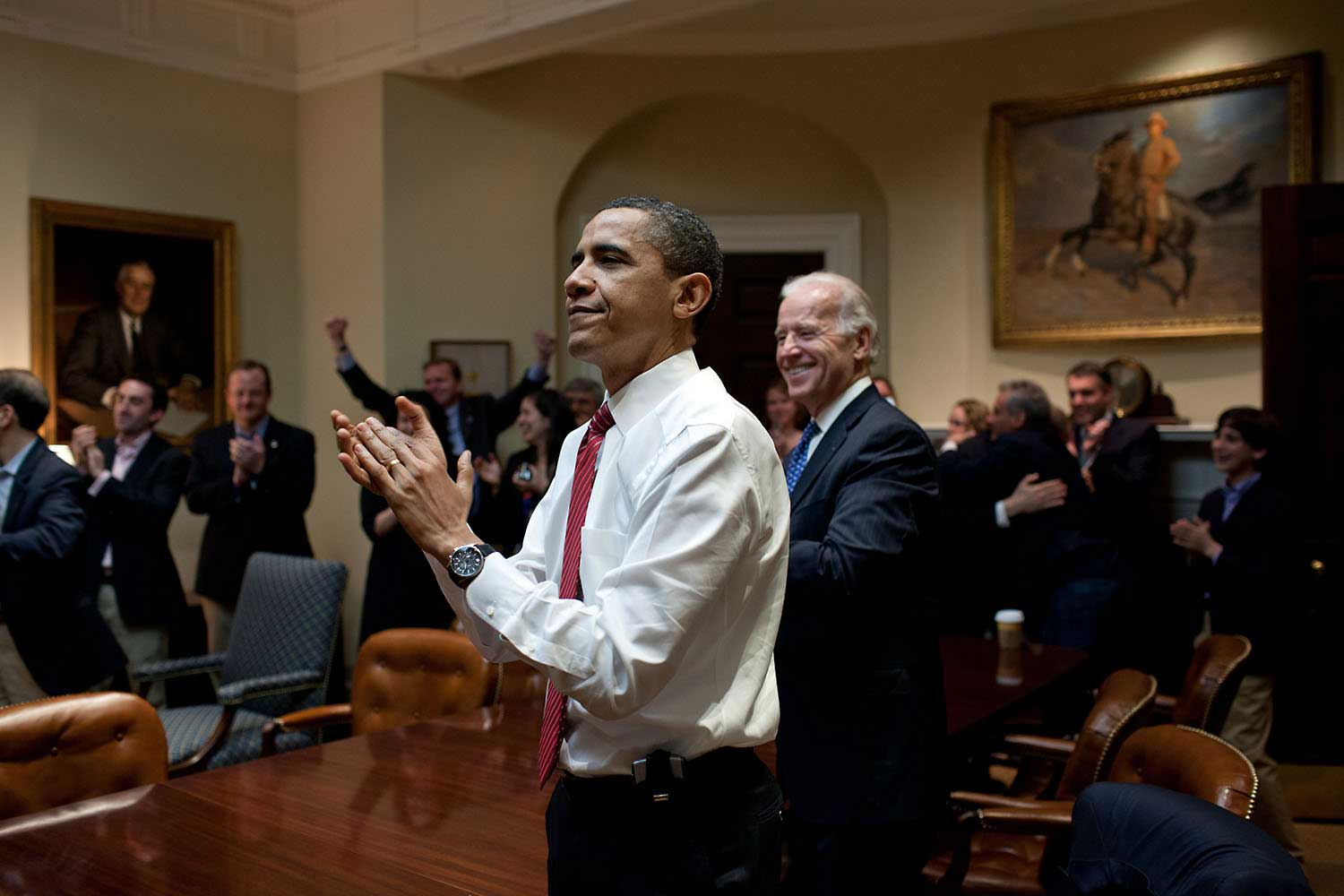 The President, Vice President and senior staff applaud after watching on television the House vote on H.R. 4872 for health care reform, in the Roosevelt Room of the White House, March 21, 2010.