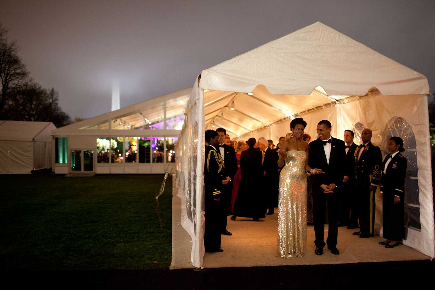 """The President and First Lady wait for Indian Prime Minister Singh's motorcade to depart the White House at the conclusion of the first official state dinner for the Obama administration, Nov. 24, 2009. The dinner was held in a tent on the South Lawn. The mist and fog made for an interesting scene, even obscuring the top of the Washington Monument in the background."""