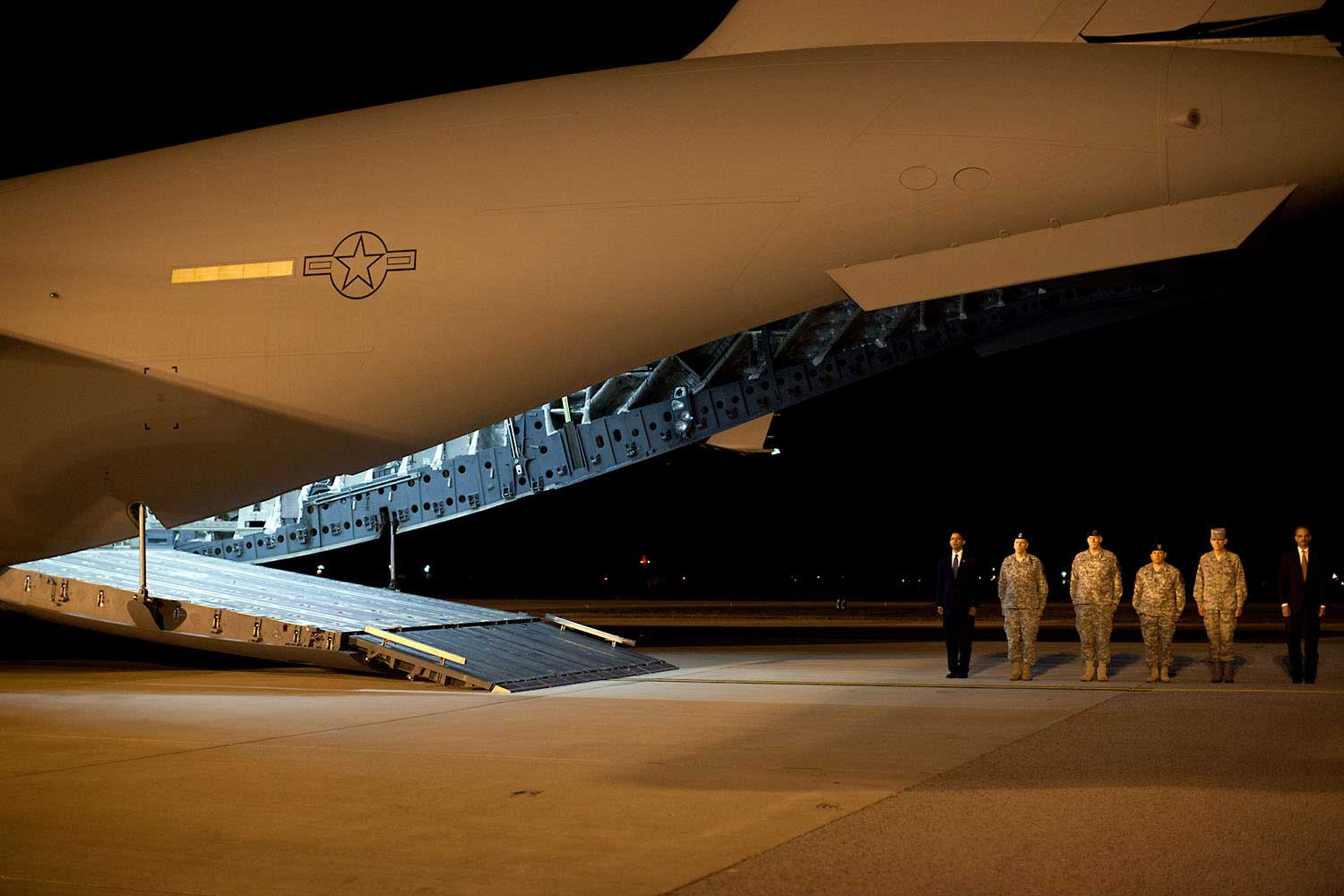 """This photo was taken about 4AM, Oct. 29, 2009, after the President made an unannounced trip to Dover Air Force Base to pay respects to fallen troops coming back from Afghanistan. After meeting privately with the families, the President walked alone up the ramp of the cargo plane carrying the 18 caskets, all draped in American flags. I could see the emotion on his face as he walked from casket to casket, leaving a Presidential coin on each. When he was done, he paused for a few minutes, head bowed in prayer. I heard him tell others later how that was the most difficult moment of his Presidency thus far. Out of respect for the families, not all of who wanted their ceremony photographed, we can't show those pictures (but they will become part of Presidential archive.)"
