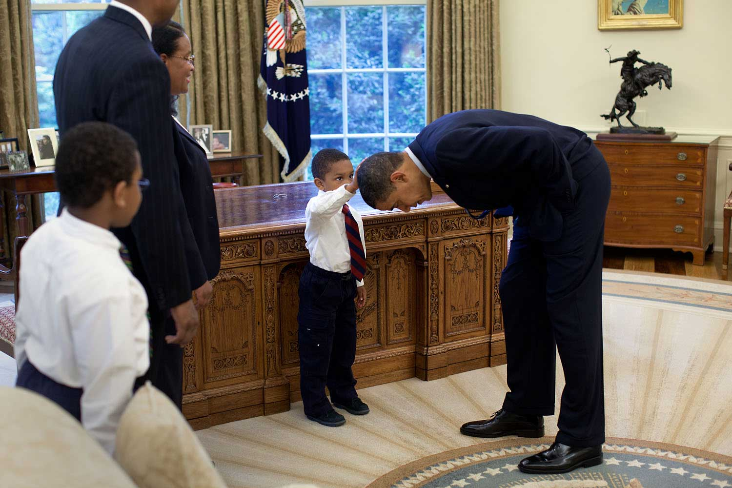 """A National Security staffer, Carlton Philadelphia, brought his family to the Oval Office for a farewell photo with President Obama. Carlton's son, Jacob, softly told the President he had just gotten a haircut like President Obama, and asked if he could feel the President's head to see if it felt the same as his."""