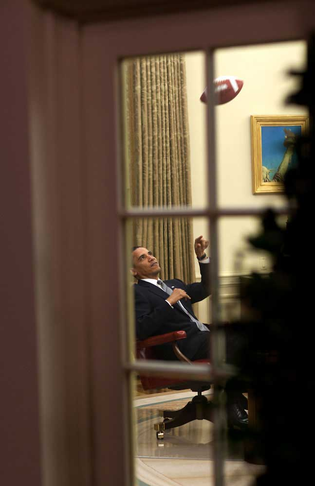 The President throws a football to an aide before a meeting in the Oval Office, April 23, 2009.