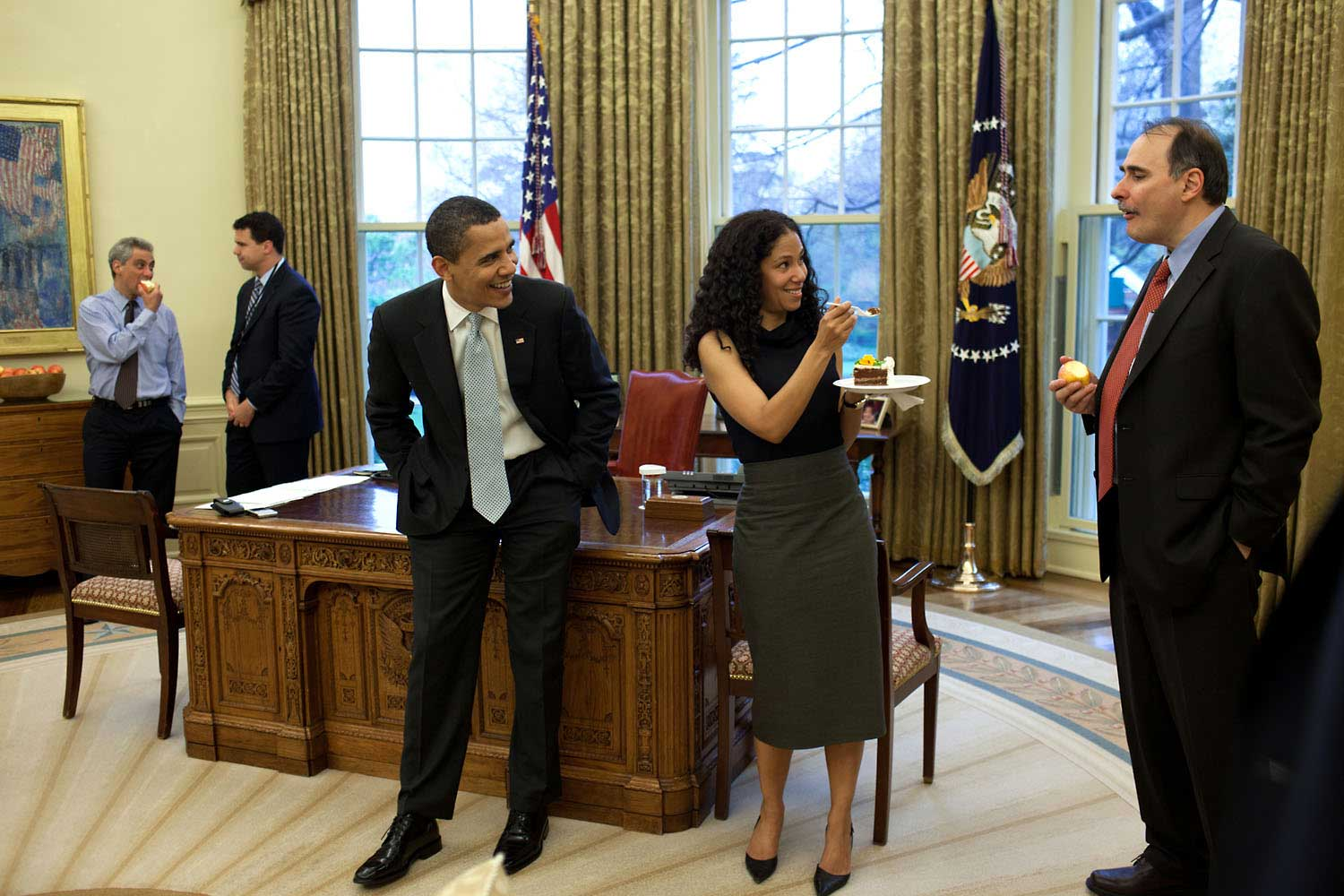 Deputy chief of staff Mona Sutphen jokingly offers a piece of birthday cake to senior advisor David Axelrod as the President watches amusingly in the Oval Office, April 15, 2009. The party was held to commemorate senior advisor Pete Rouse's birthday.