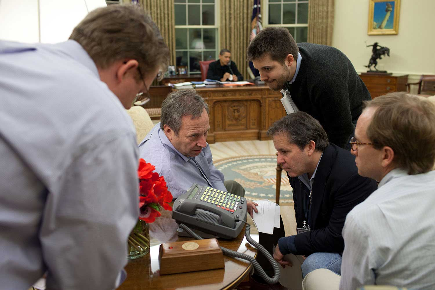 On Sunday night, March 29, 2009, aides listen to a speaker phone as the President made calls to alert officials about his plan to set deadlines for General Motors and Chrysler overhauls that were to be announced the next day.