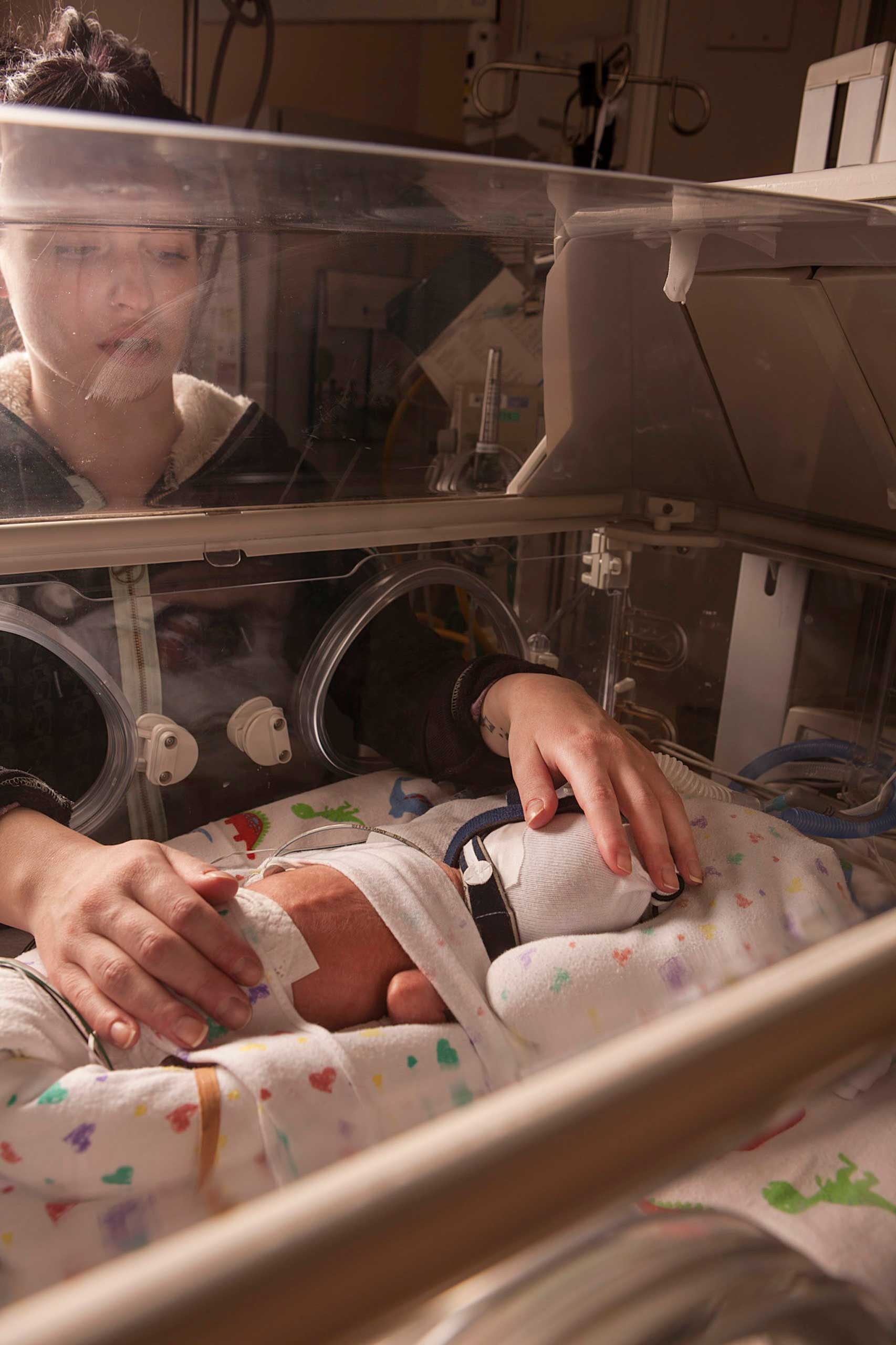 Melissa, David's mother, touches him as he lies in an incubator at the Children's Hospital of Wisconsin.