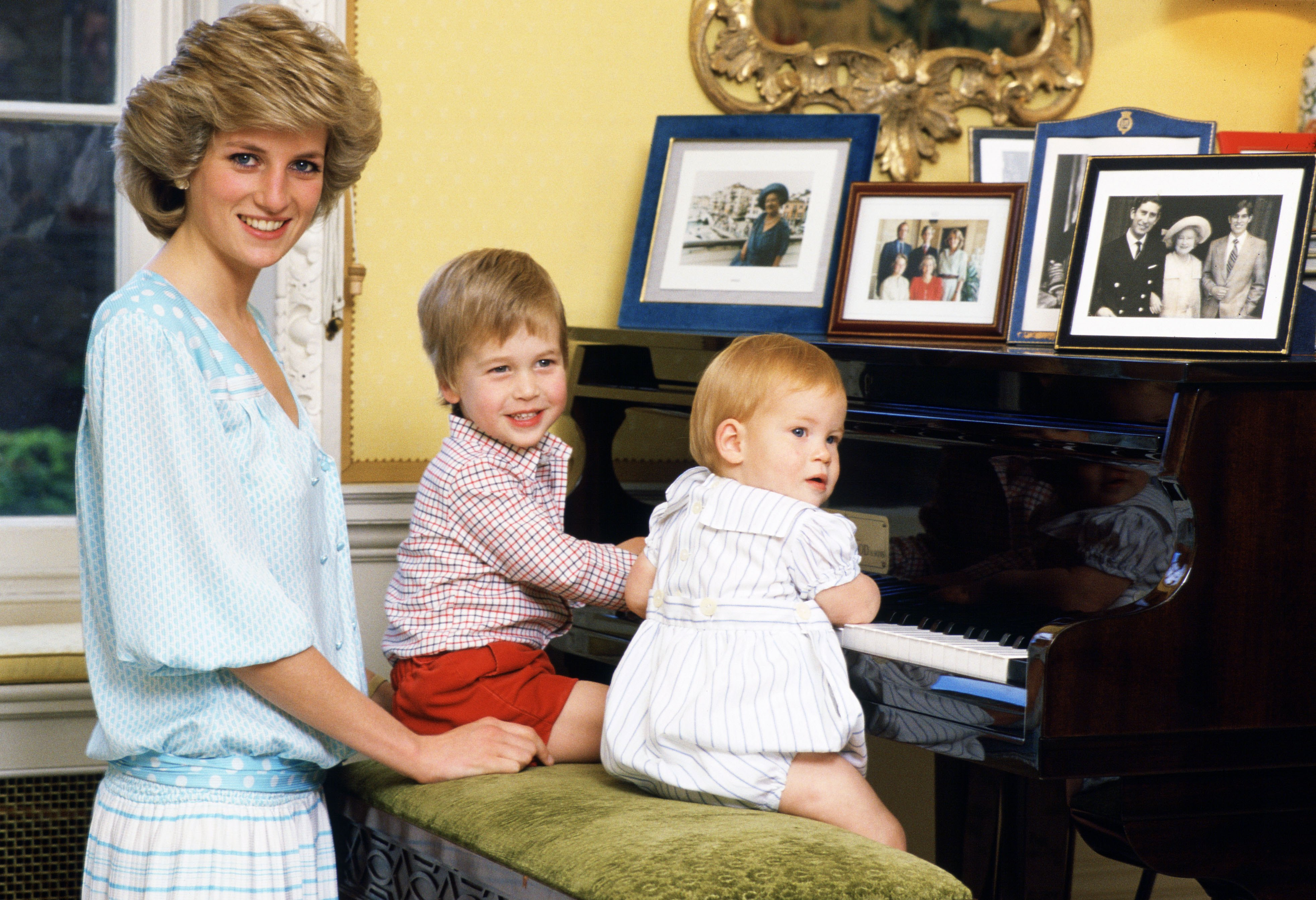 Diana, Princess of Wales with her sons, Prince William and Prince Harry, at the piano in Kensington Palace, London on Oct. 4, 1985.