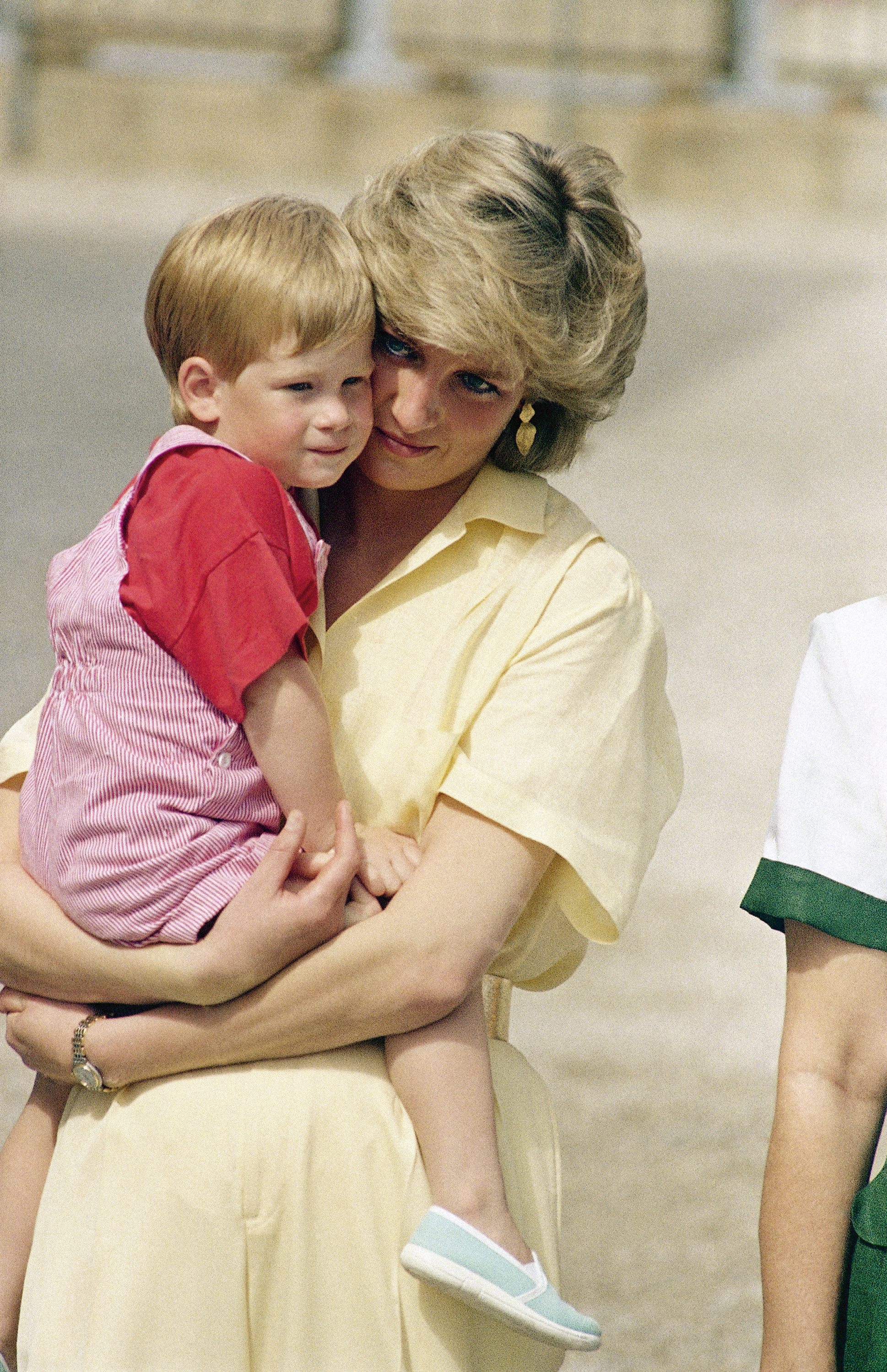 The Princess of Wales holds son Prince Harry while the royal family poses for photographers at the Royal Palace in Majorca, Spain on Aug. 9, 1987.