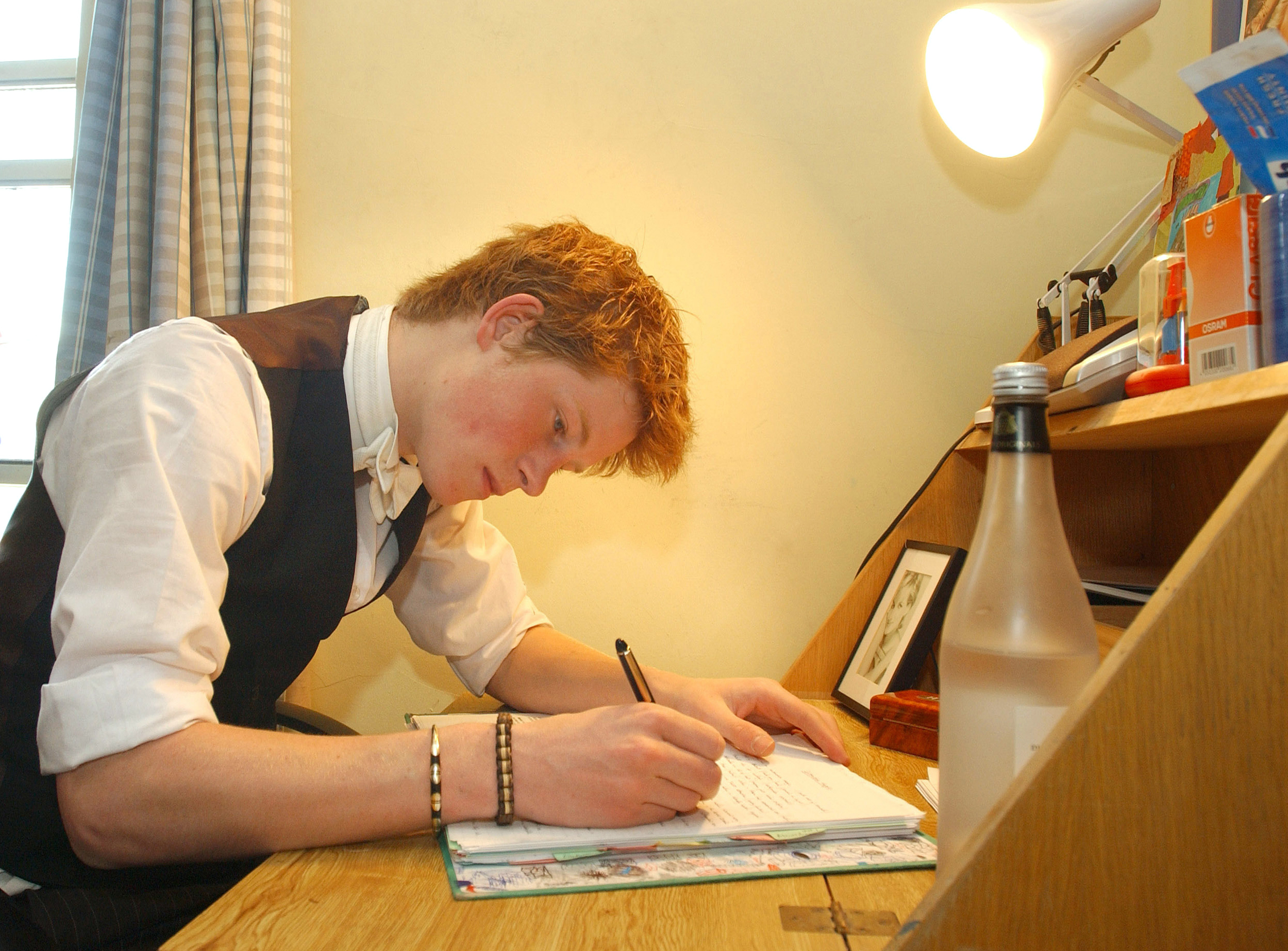 Prince Harry writes at his desk in his room at Eton College boarding school on June 7, 2003 in Berkshire, England.