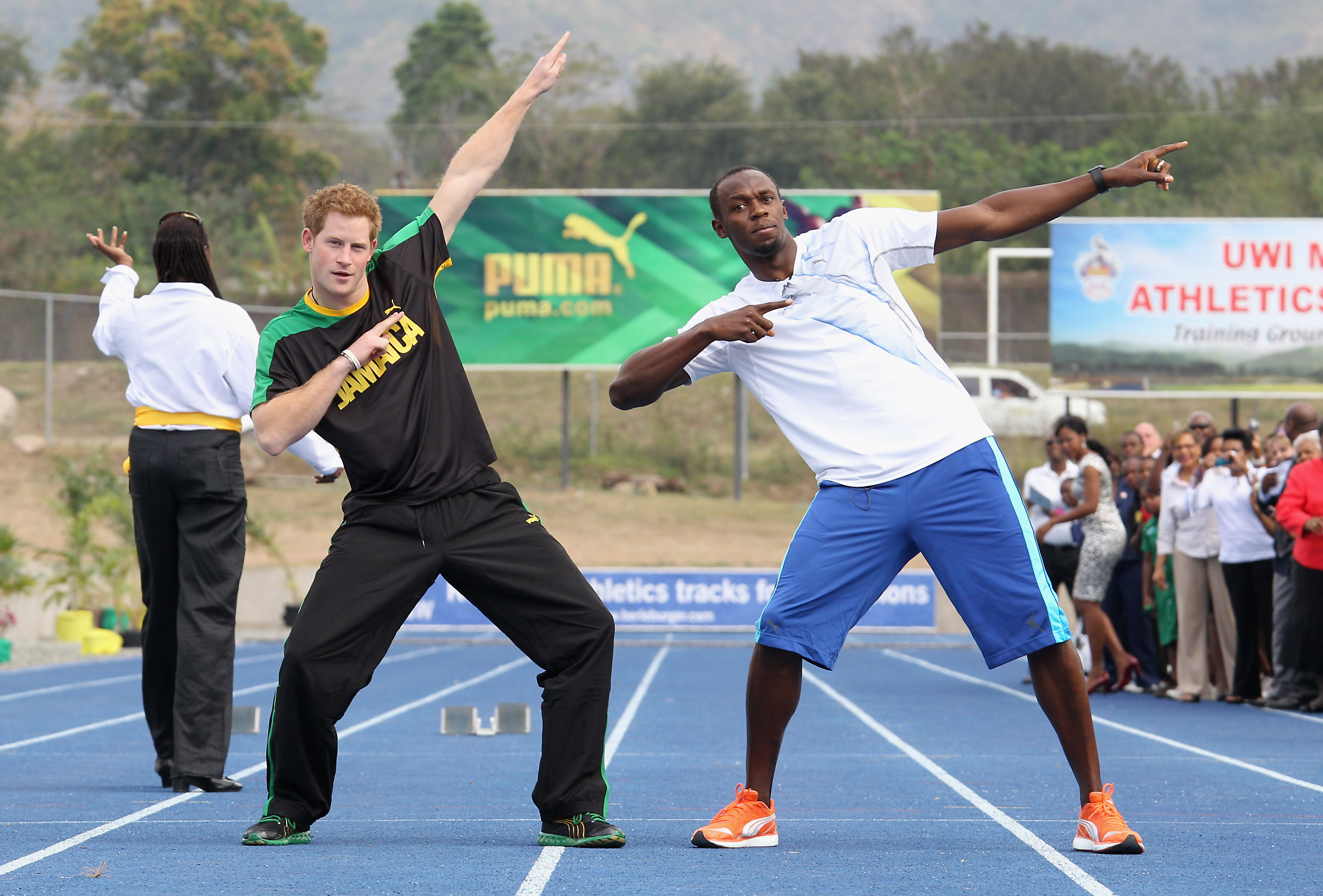 Prince Harry poses with Usain Bolt at the Usain Bolt Track at the University of the West Indies on March 6, 2012 in Kingston, Jamaica.