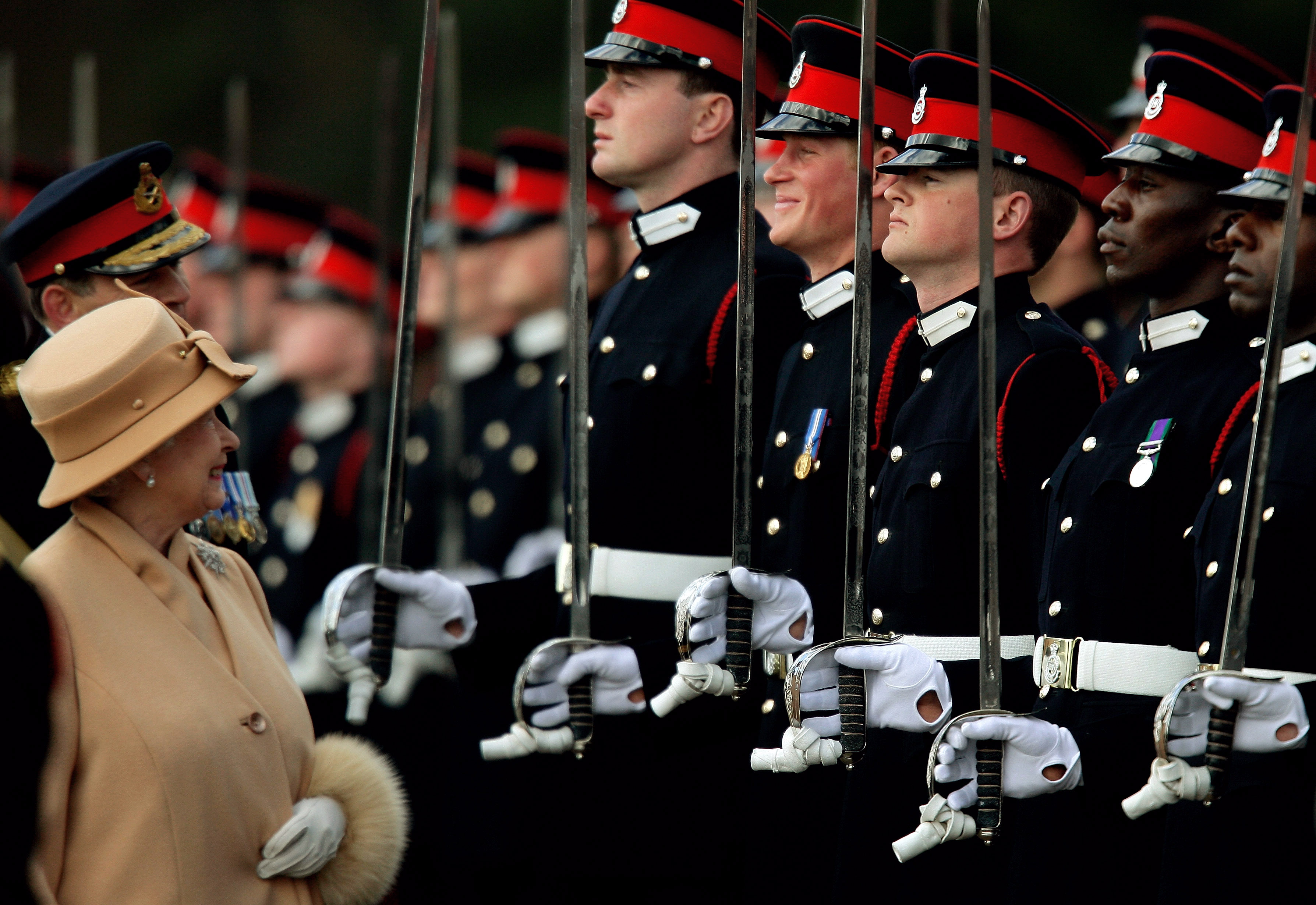 Queen Elizabeth smiles with Prince Harry during the Sovereign's Parade at the Royal Military Academy in Sandhurst, southern England on April 12, 2006.