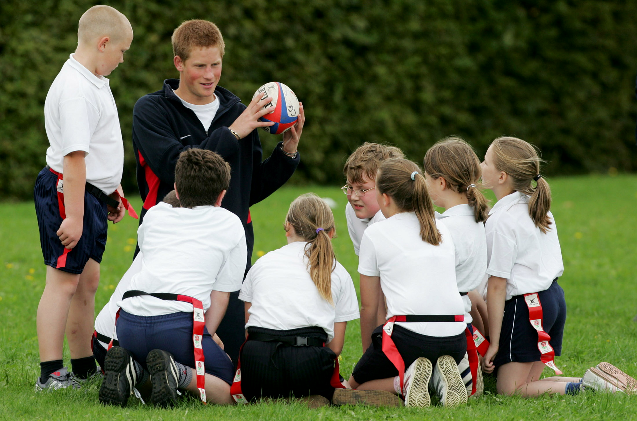 Prince Harry teaches rugby to a group of 10 and 11-year-old pupils from Shelfield Primary School in Walsall in central England on Sept. 28, 2004.