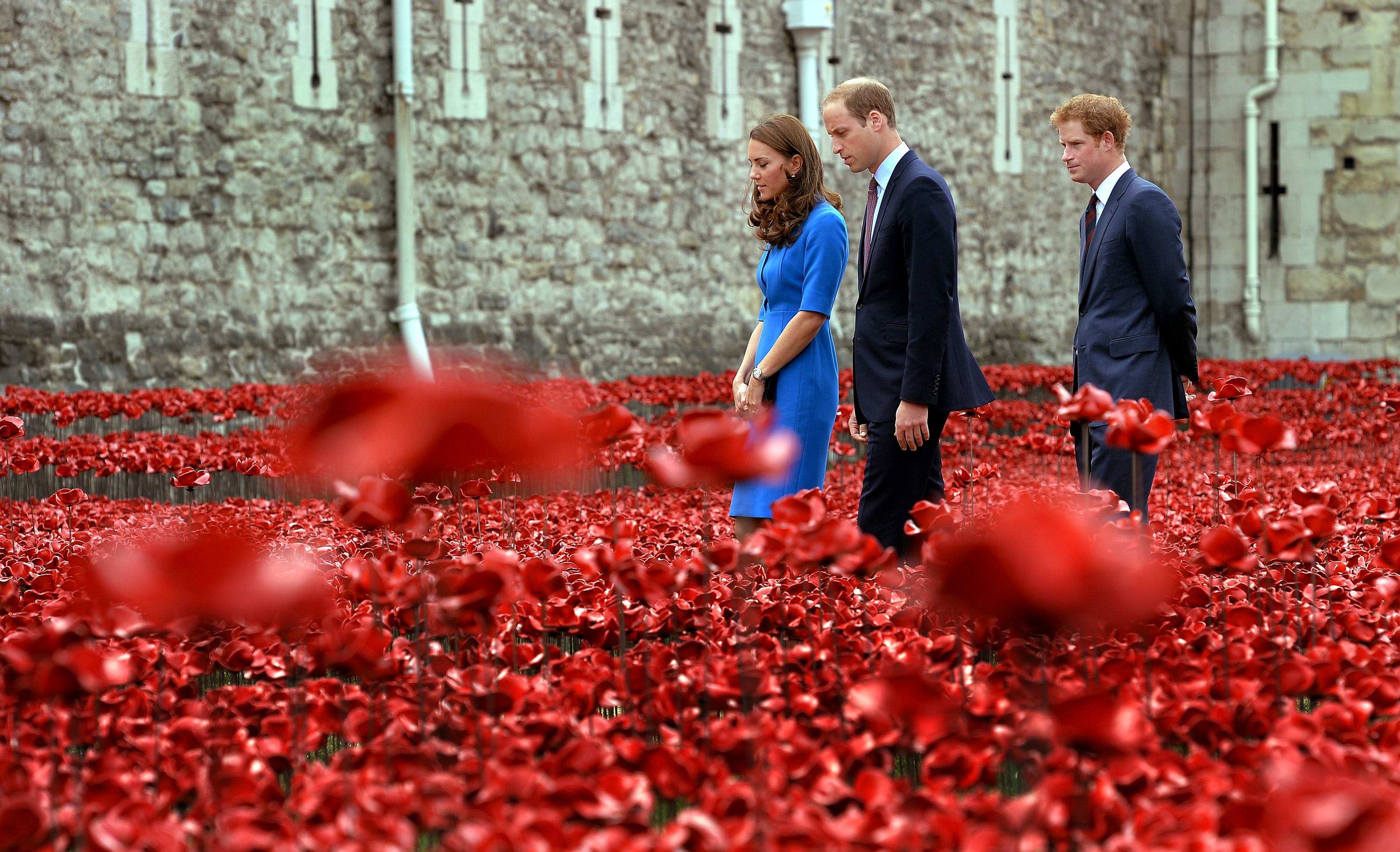 """The Duke and Duchess of Cambridge and Prince Harry view the Tower of London's """"Blood Swept Lands and Seas of Red"""" Poppy Installation to commemorate the 100th Anniversary of the outbreak of the First World War at the Tower of London on Aug. 5, 2014."""