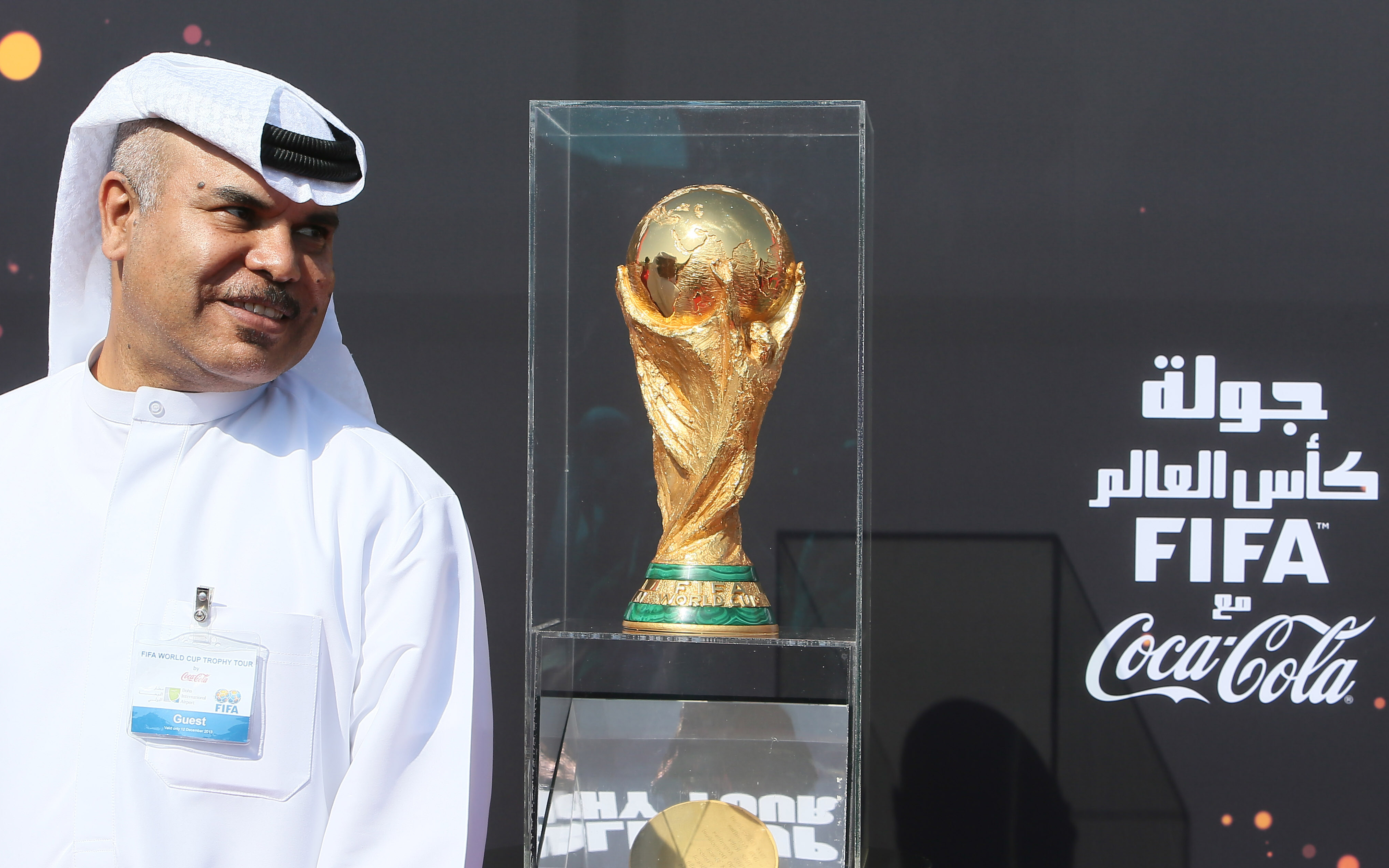 A Qatari official stands near the FIFA World Cup trophy following its arrival in Doha, on Dec. 12, 2013.