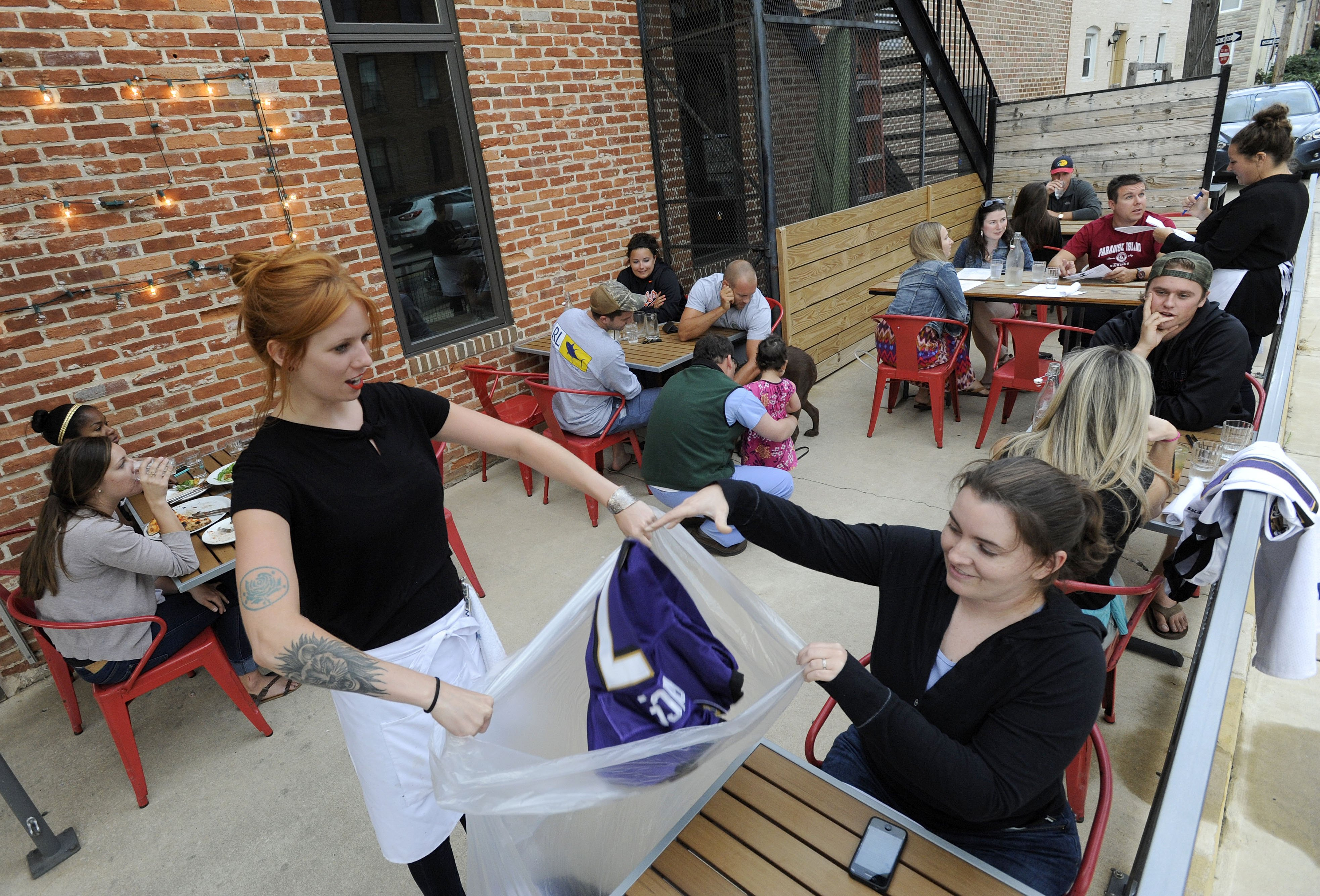 Bartender Abby Hopper, left, of Baltimore, collects a Ray Rice Baltimore Ravens football jersey from Erin McGonigle, right, of Arbutus, Md., at Hersh's Pizza and Drinks, a Baltimore restaurant that offered a free personal pizza in exchange for Rice jerseys on Sept. 8, 2014.