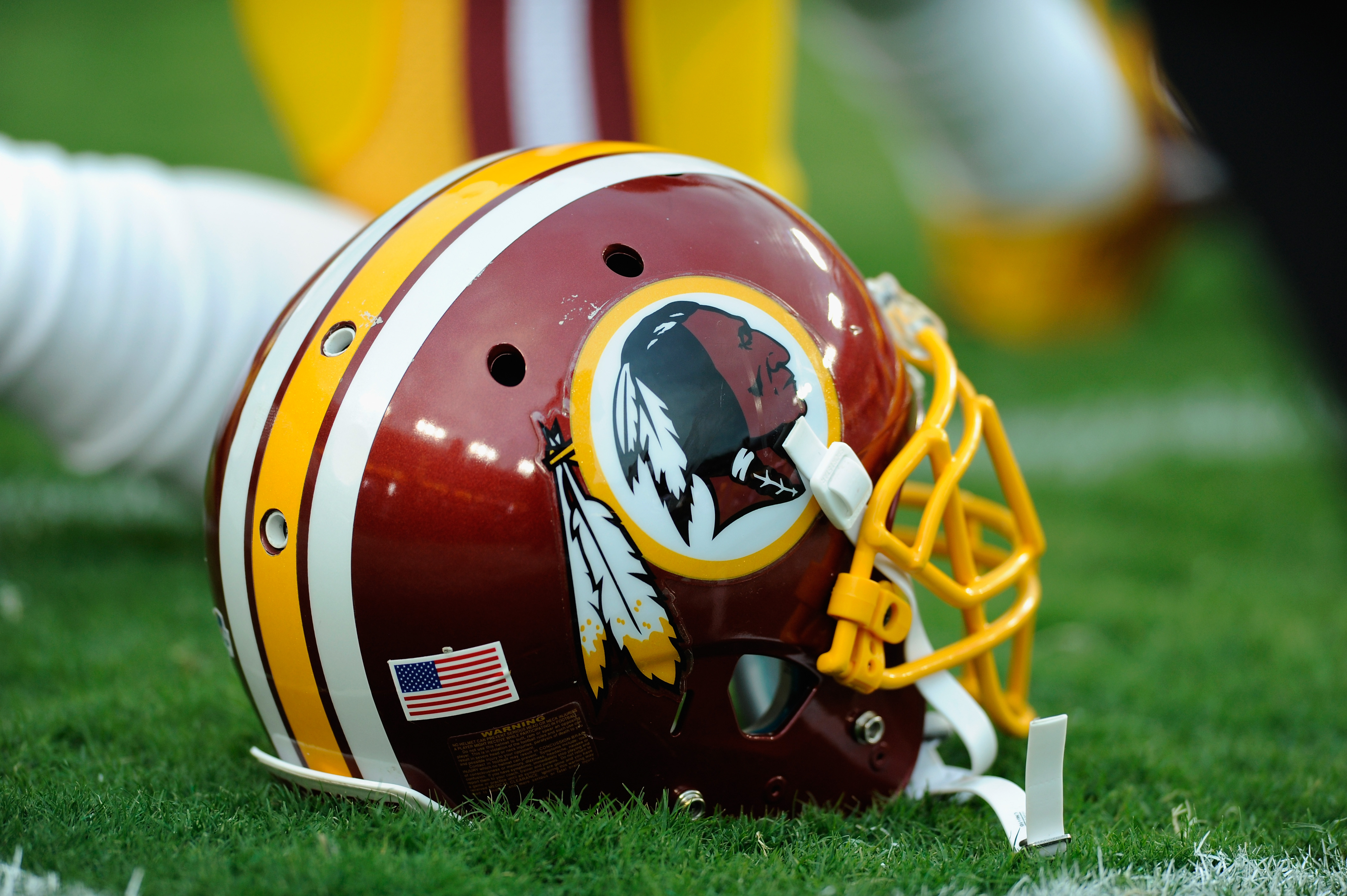 A Washington Redskins helmet sits on the grass during a preseason football game between the Redskins and Cleveland Browns at FedExField on August 18, 2014 in Landover, Maryland.
