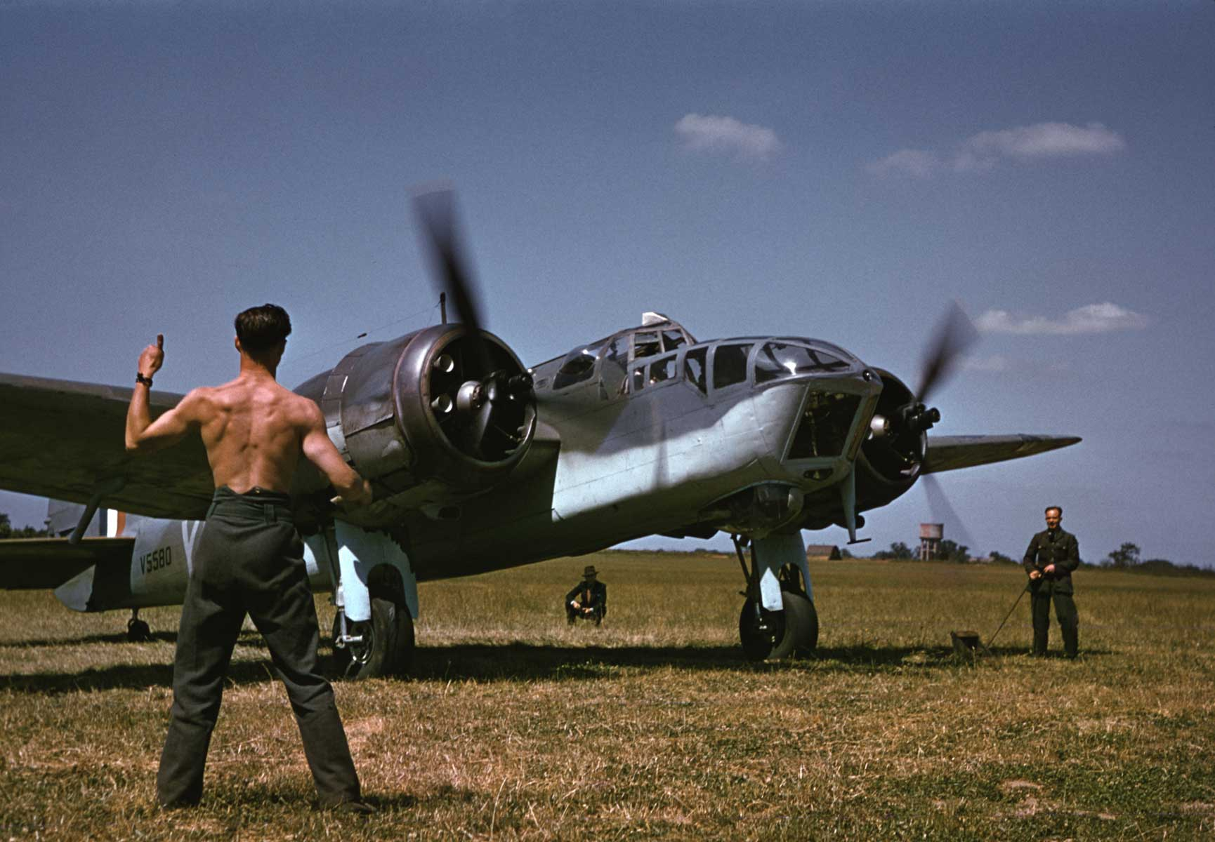 A mechanic signals for takeoff to an Allied pilot before a raid over Occupied France, England, 1941.