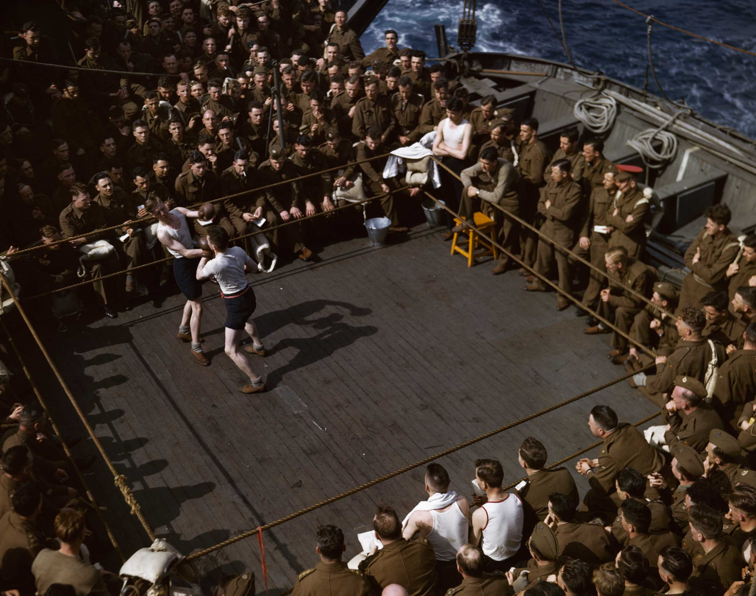 British soldiers watching a boxing match on a troop ship from England to North Africa, 1943.