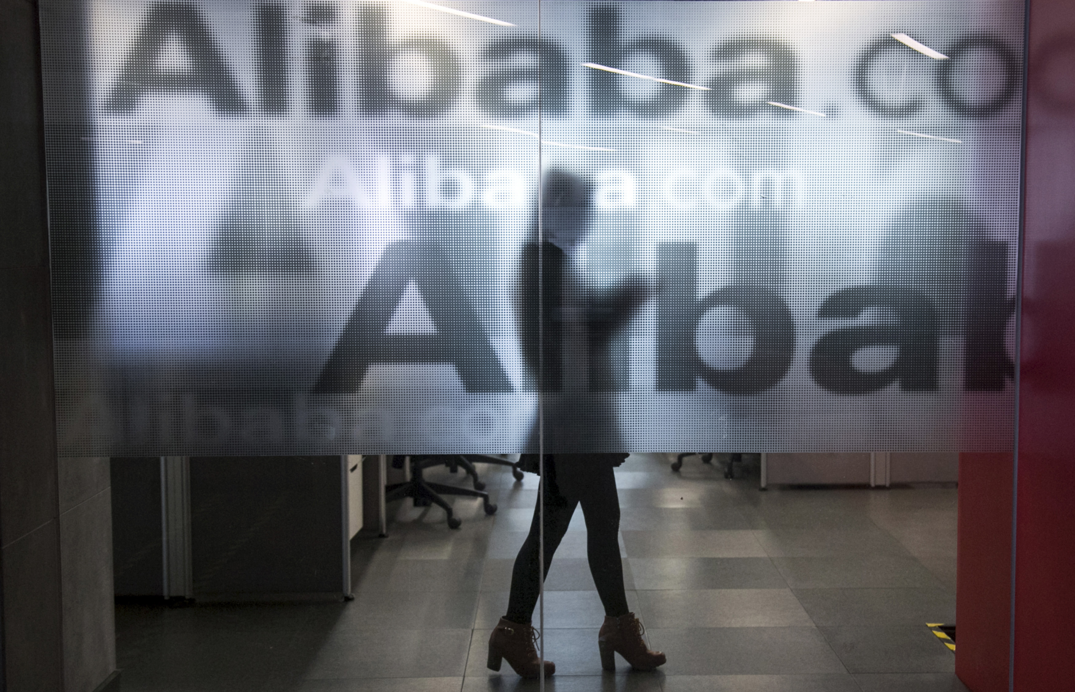 An employee is seen behind a glass wall at Alibaba's headquarters on the outskirts of Hangzhou, China, on April 23, 2014