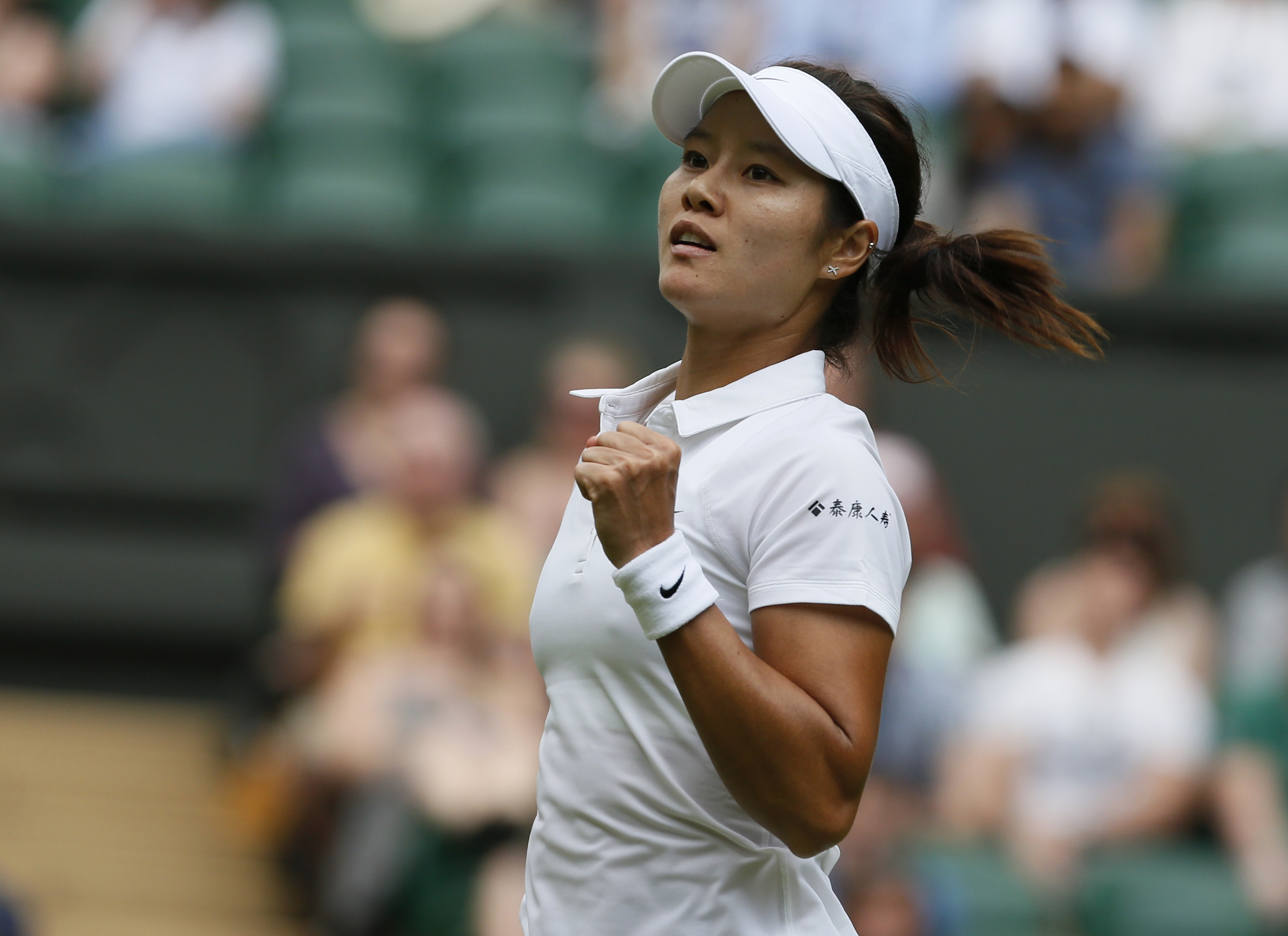 Li Na of China reacts after defeating Paula Kania of Poland in their women's singles tennis match at the Wimbledon Tennis Championships, in London June 23, 2014.