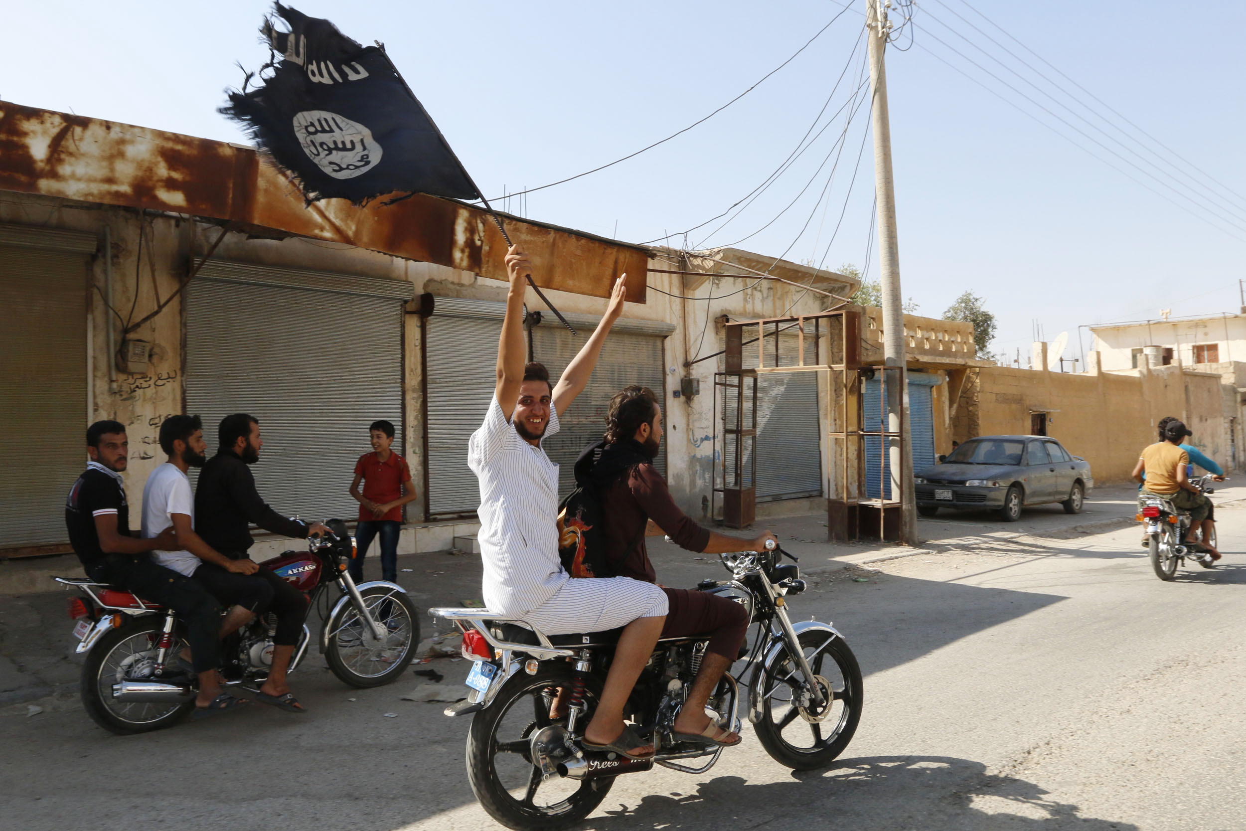 A resident of Tabqa city touring the streets on a motorcycle celebrates after Islamic State of Iraq and Greater Syria militants took over Tabqa air base, in the nearby Syrian city of Raqqa on  Aug. 24, 2014