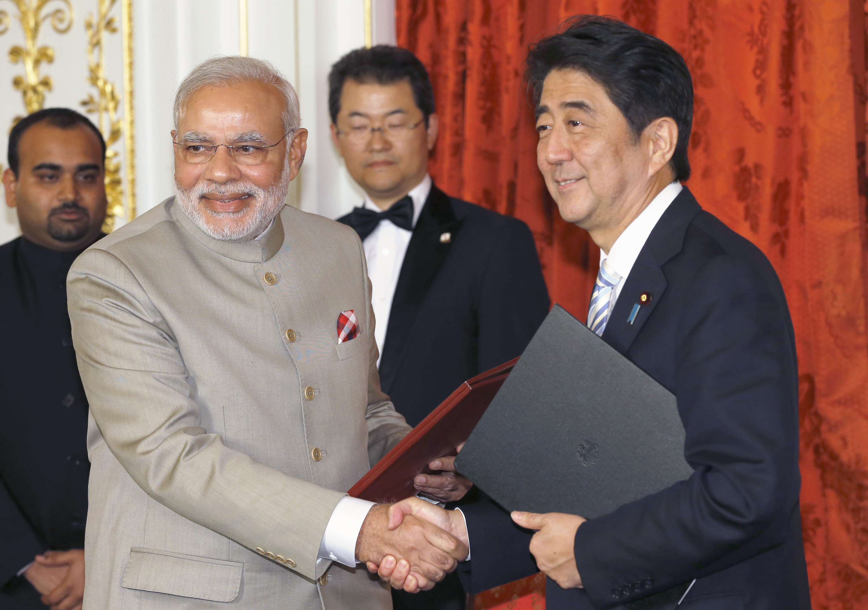 India's Prime Minister Narendra Modi, left, shakes hands with Japan's Prime Minister Shinzo Abe during a signing ceremony in Tokyo on Sept. 1, 2014