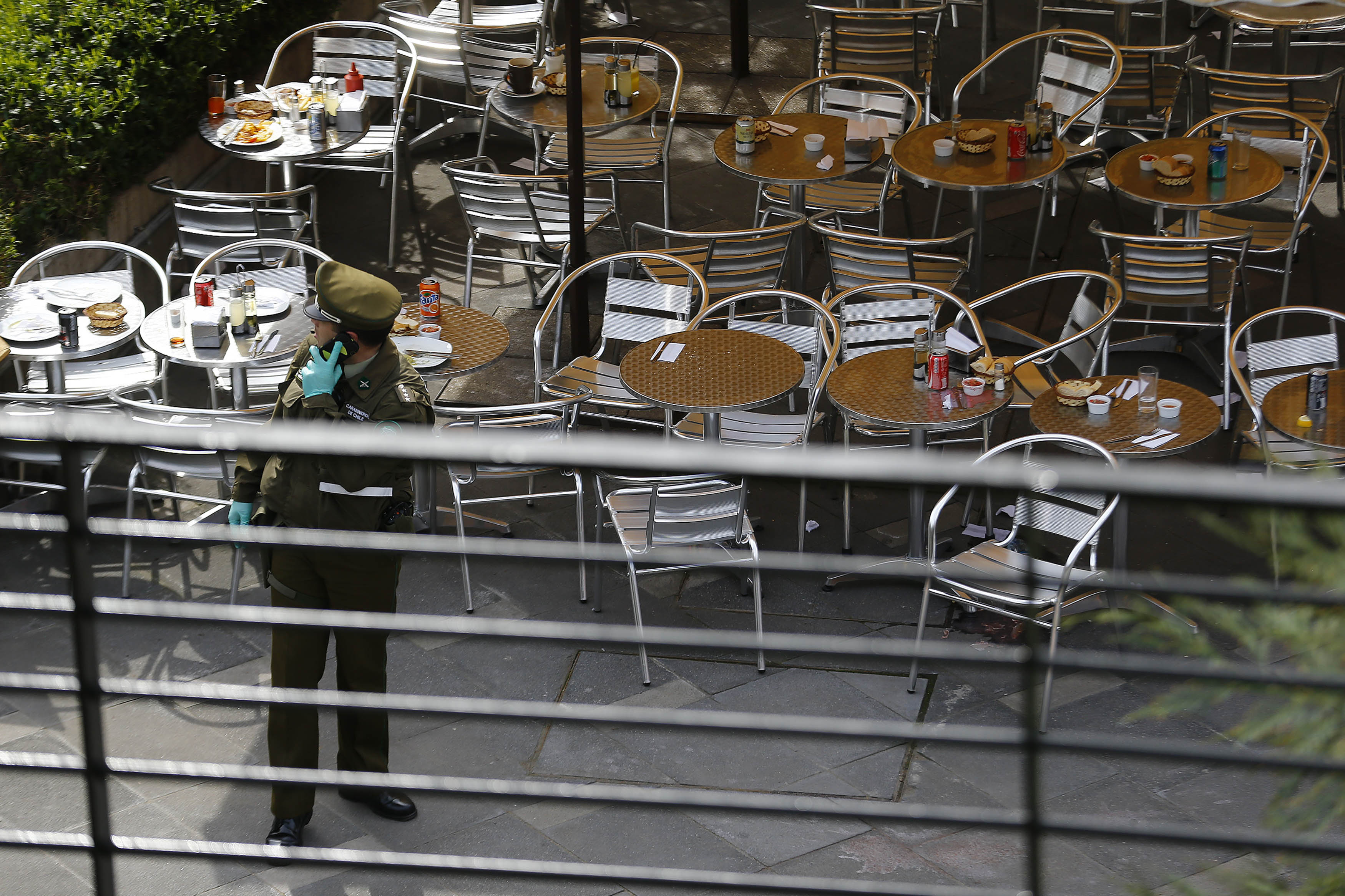 A police officer talks on his cell phone at the area where a bomb exploded in Santiago, Chile, on Sept. 8, 2014