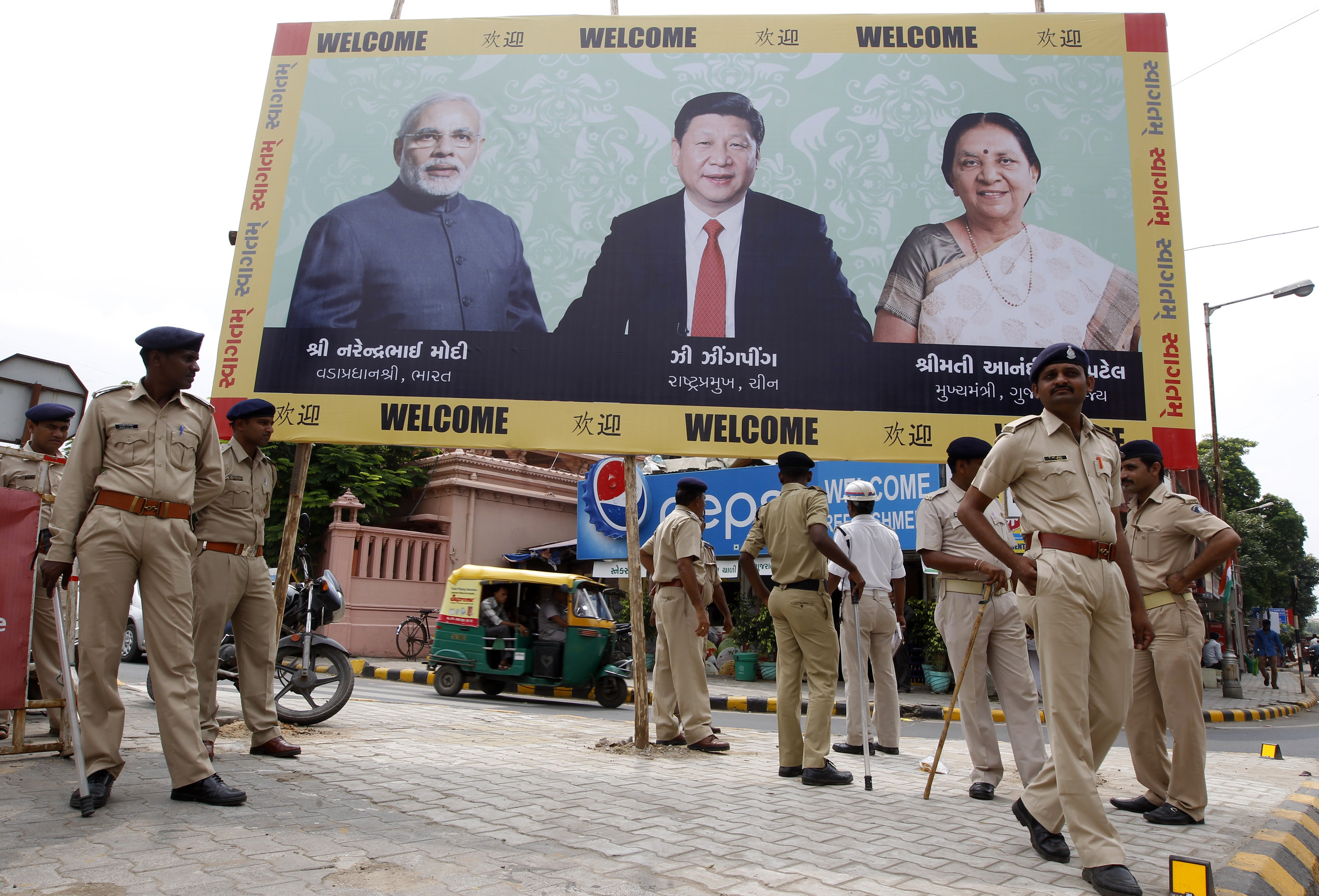 Police personnel stand guard on Sept. 16, 2014, in front of a billboard with images of, from left to right, Indian Prime Minister Narendra Modi, Chinese President Xi Jinping and Gujarat Chief Minister Anandiben Patel ahead of Xi's arrival in Ahmedabad