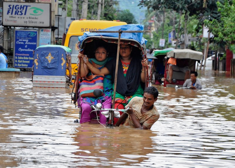 People use rickshaws to commute through a flooded road after heavy rains in the northeastern Indian city of Guwahati on Sept. 23, 2014