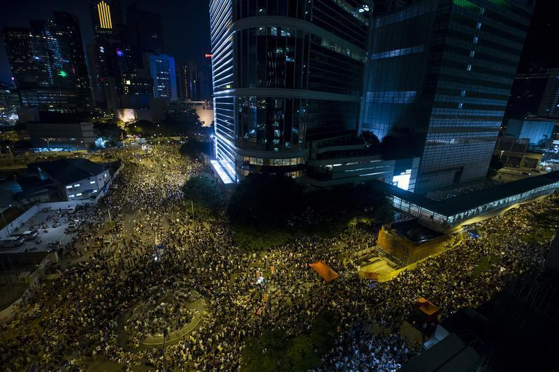 Thousands of protesters attend a rally outside the government headquarters in Hong Kong as riot police stand guard on Sept. 27, 2014