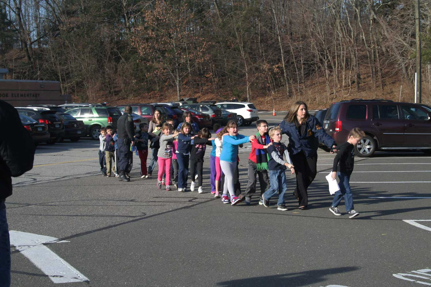 The following photos were taken on Dec. 14, 2012.                                Connecticut State Police lead a line of children from the Sandy Hook Elementary School in Newtown, Conn.