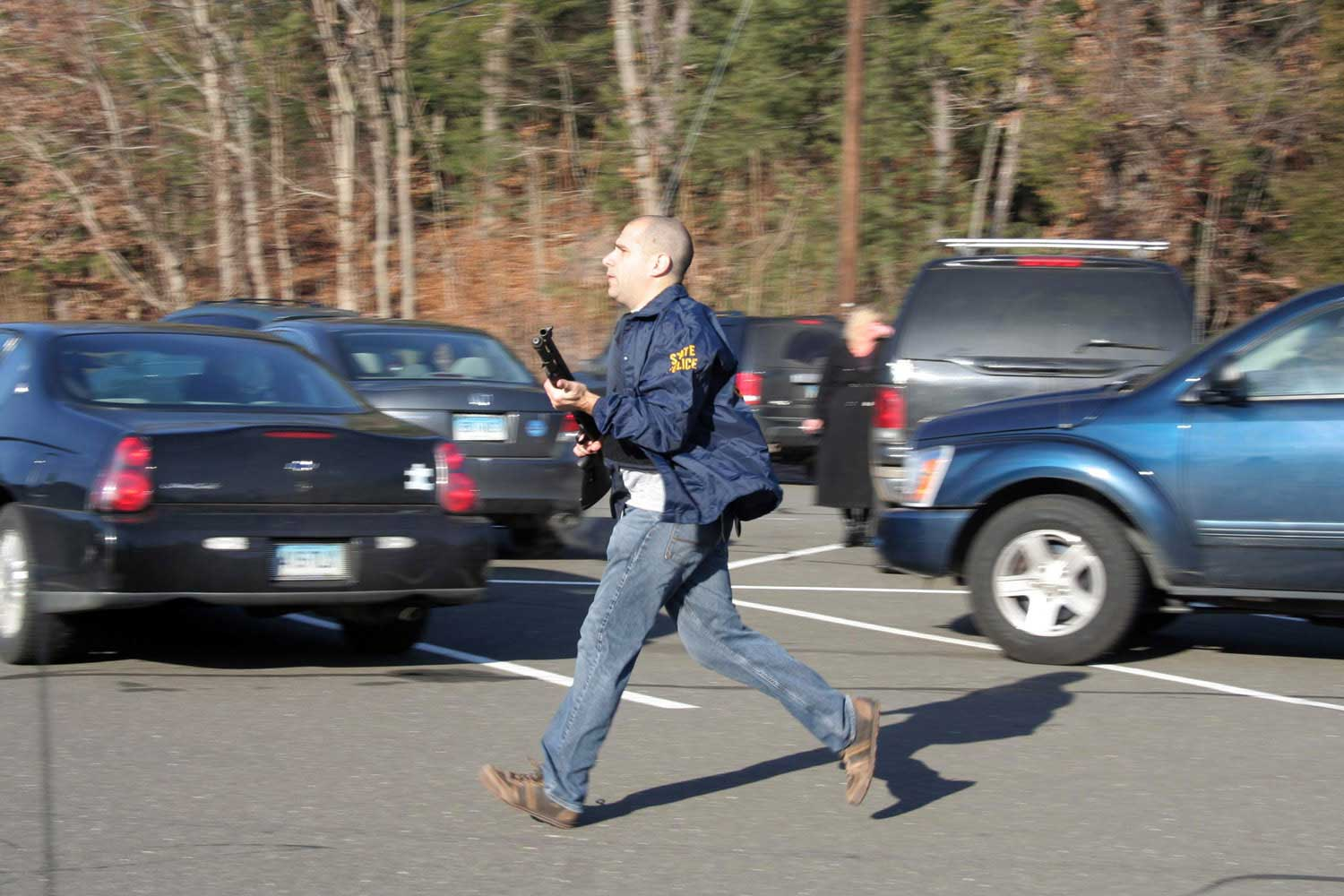 A state police officer runs outside of Sandy Hook Elementary School in Newtown, Conn.