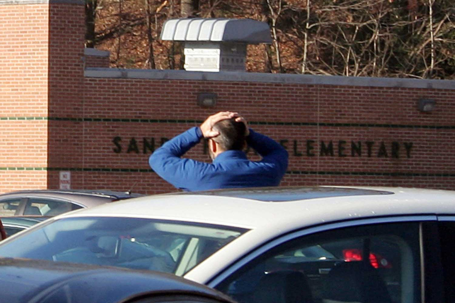 A man stands with his hands on his head outside of Sandy Hook Elementary School in Newtown, Conn.