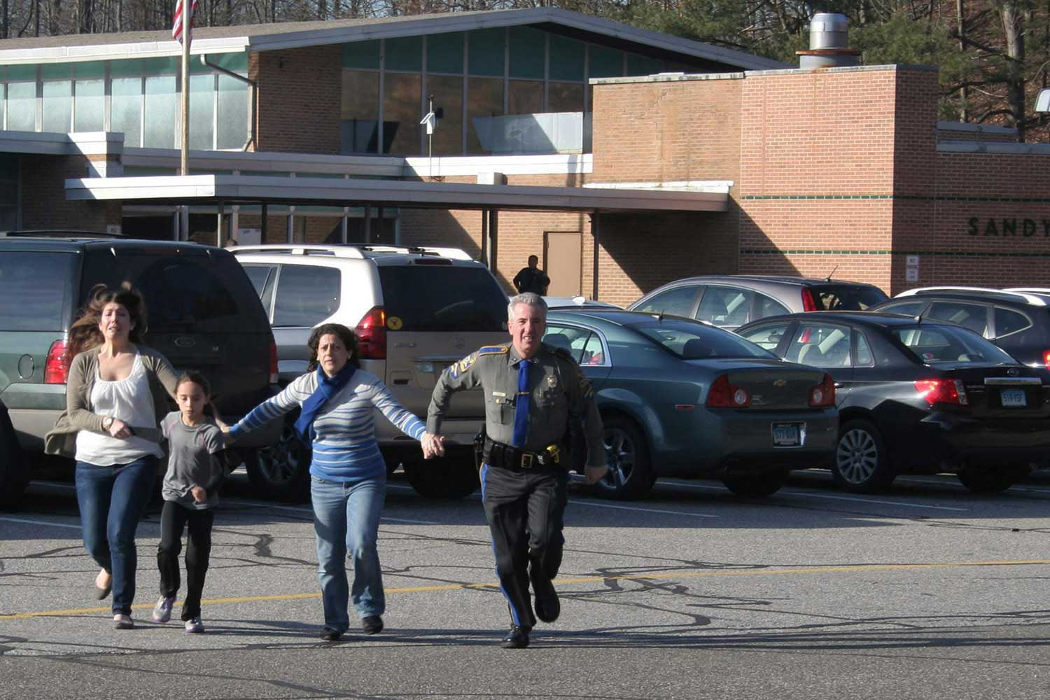A police officer leads two women and a child from Sandy Hook Elementary School in Newtown, Conn.