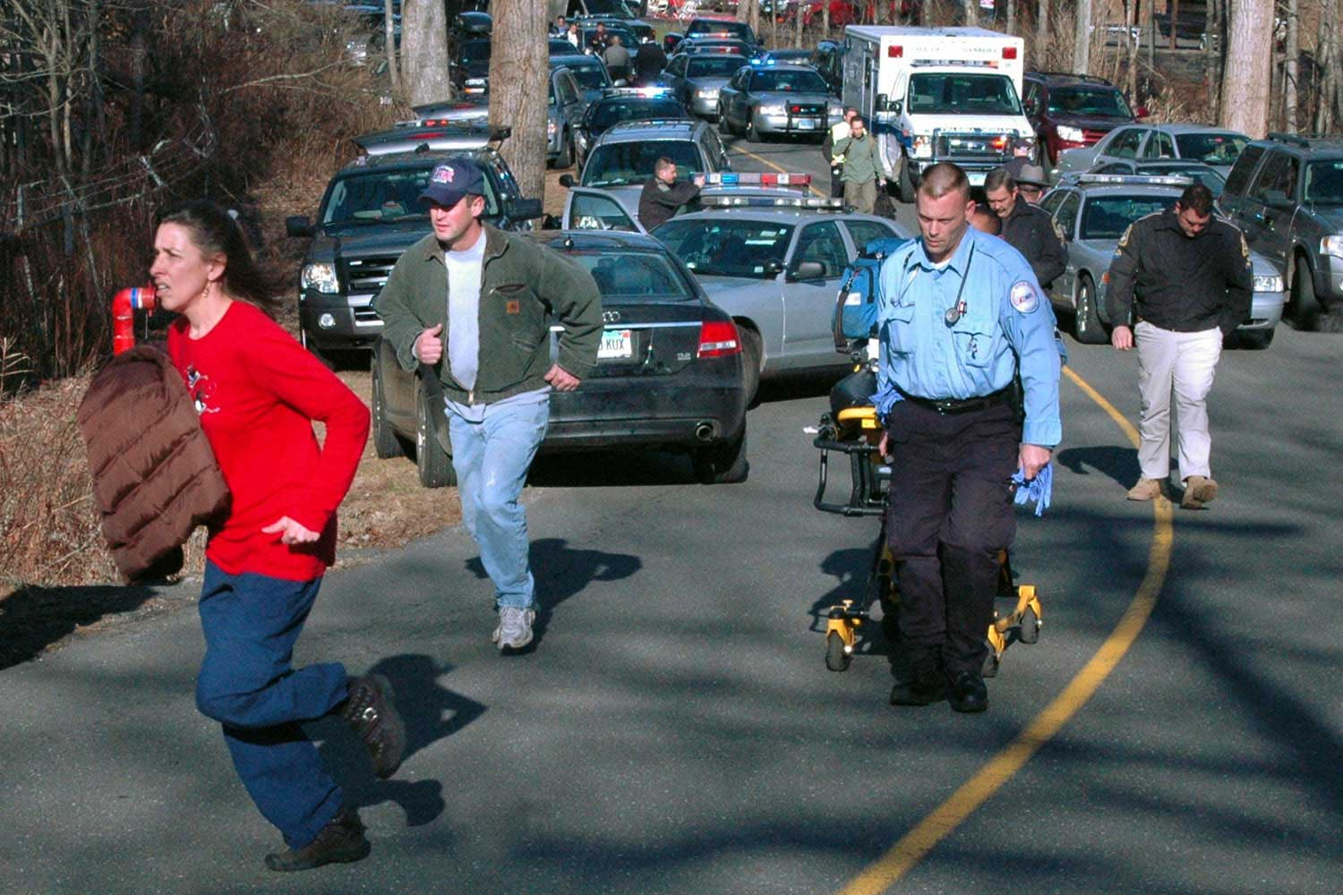 Paramedics and others rush toward Sandy Hook Elementary School in Newtown, Conn.
