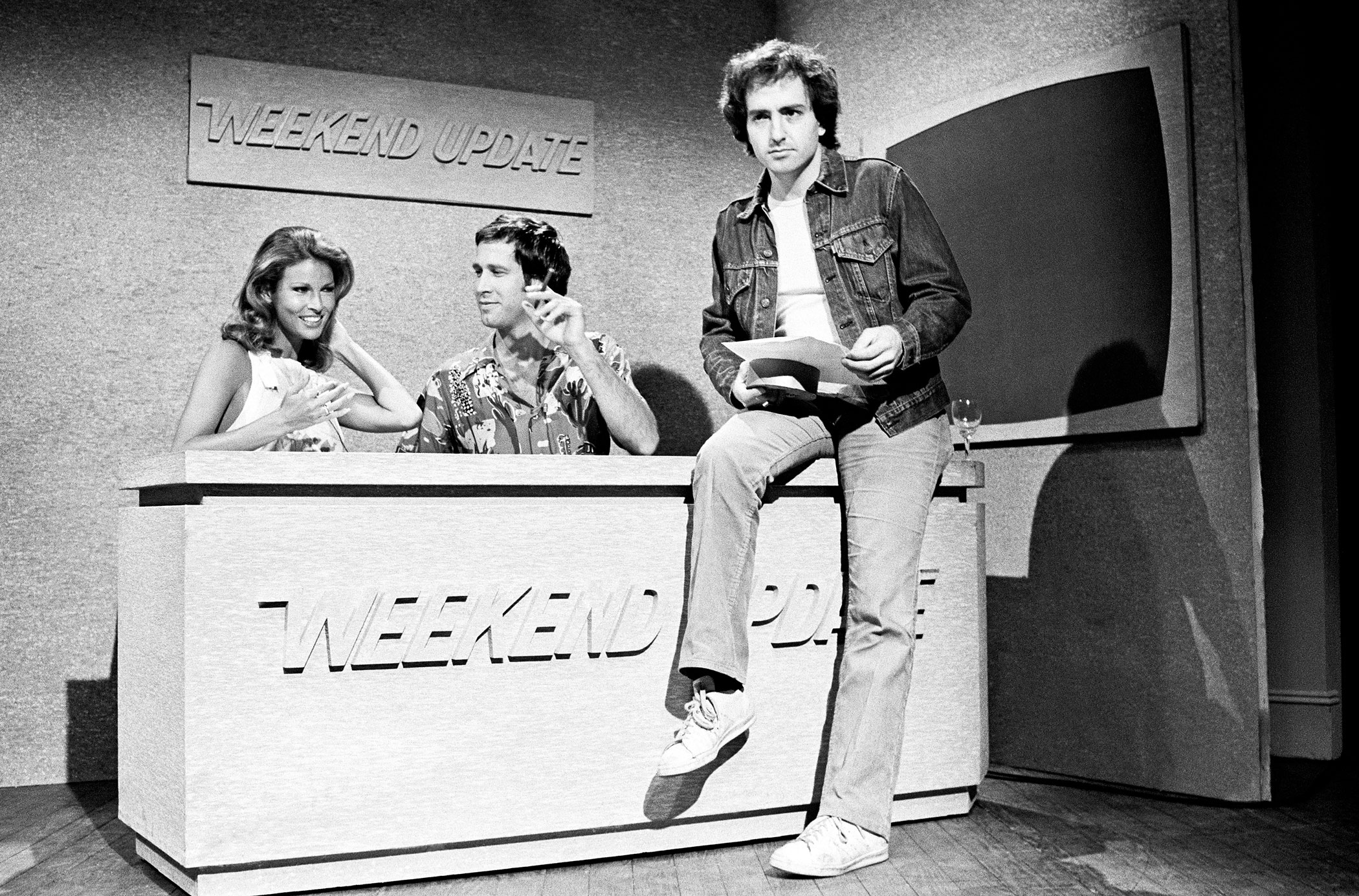 """Raquel Welch, Chevy Chase and Lorne Michaels during the """"Weekend Update"""" skit on April 24, 1976."""