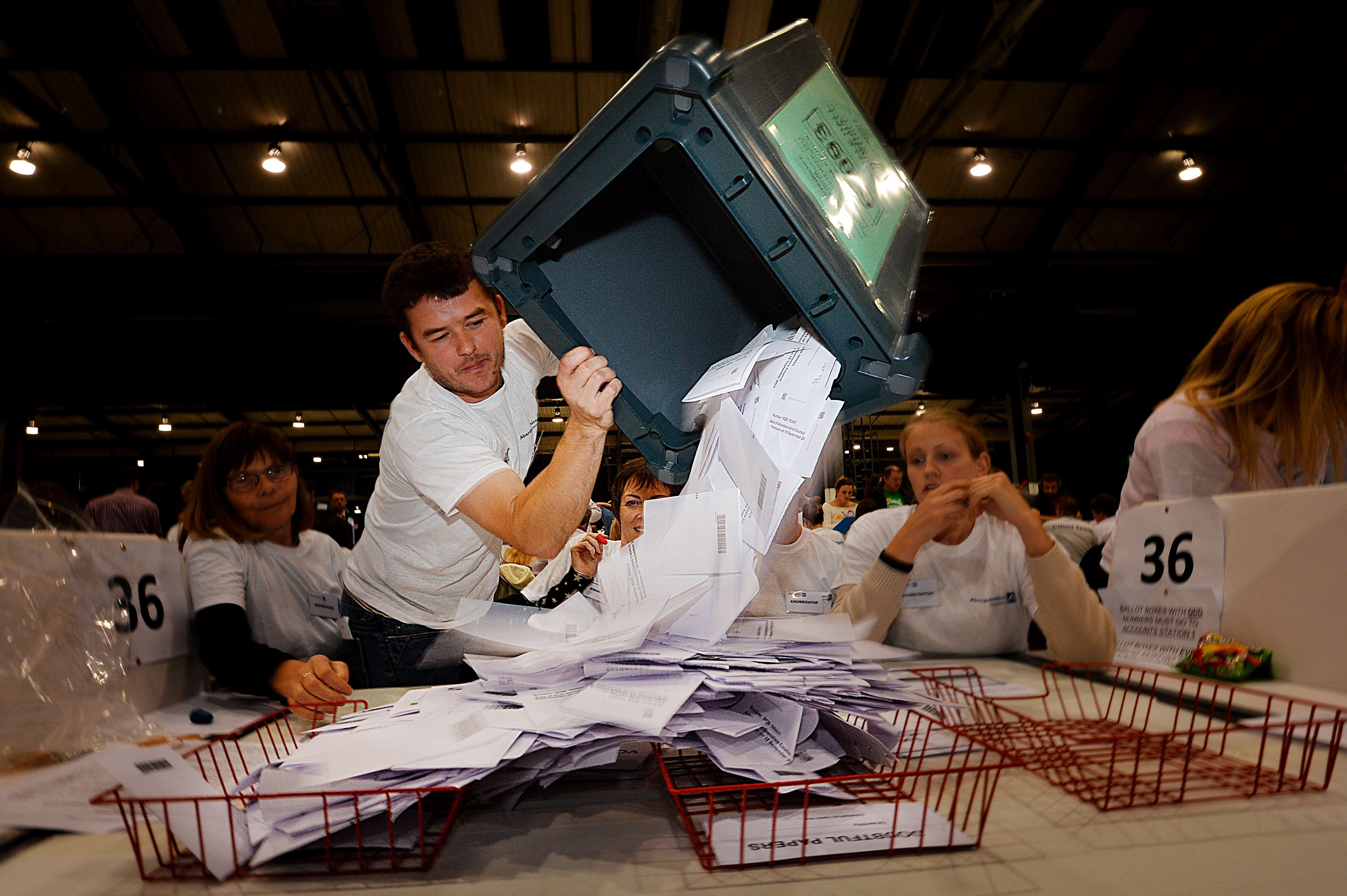 A worker tips out a ballot box in the Aberdeen Exhibition and Conference Centre in Aberdeen, Scotland, on Sept. 18, 2014, immediately after the polls close in the referendum on Scotland's independence