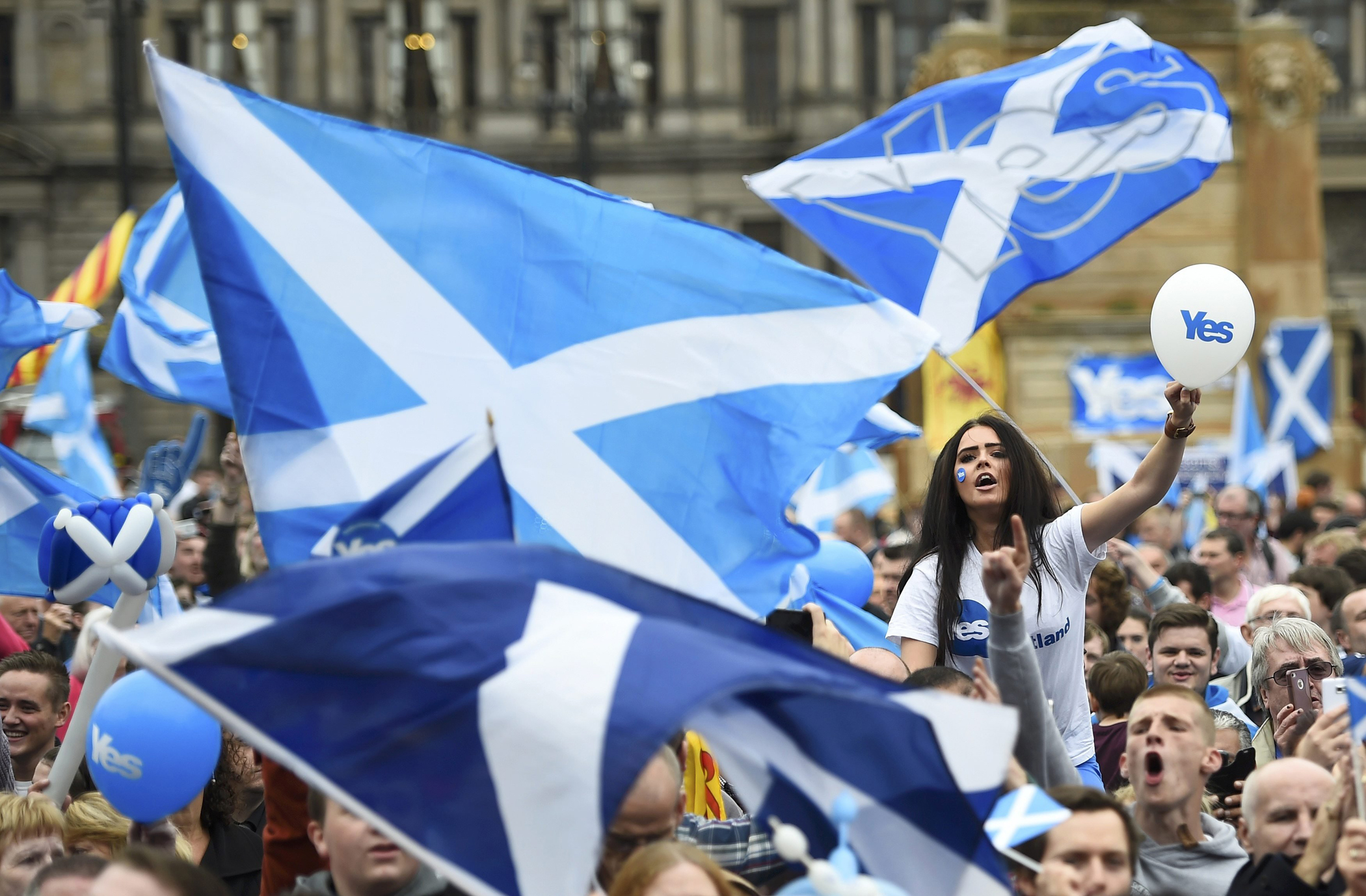 Campaigners wave Scottish Saltires at a 'Yes' campaign rally in Glasgow, Scotland, Sept. 17, 2014.