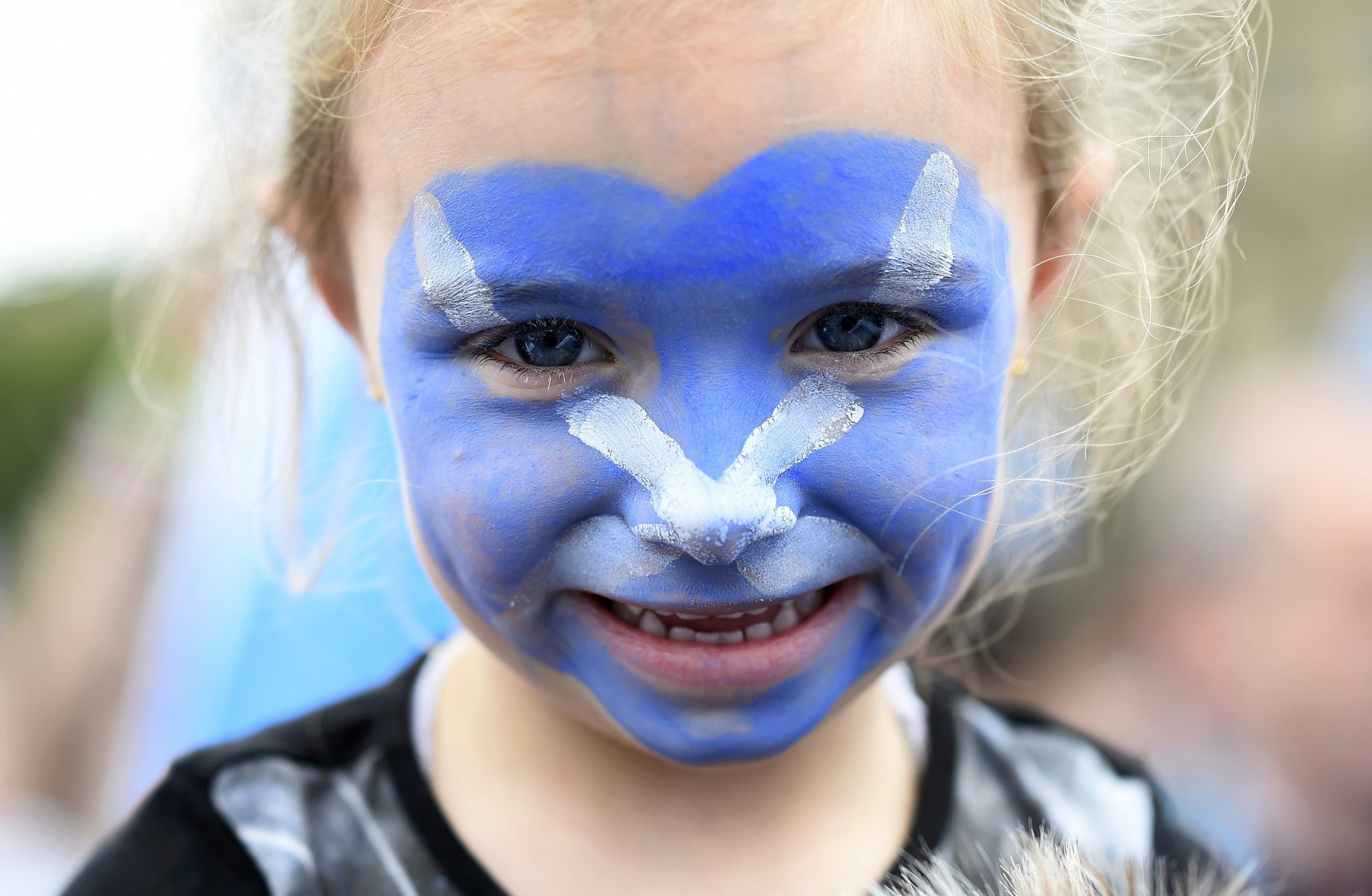A young girl with a Scottish Saltire painted on her face waits outside a 'Yes' campaign rally in Glasgow, Scotland, Sept. 17, 2014.