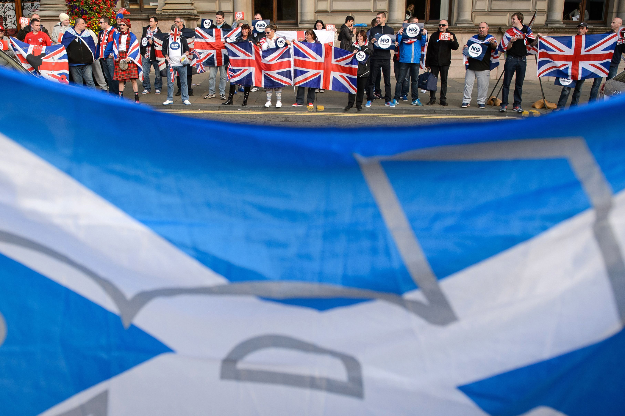 Pro-independence supporters' Scottish flag  seen in front of pro-union activists in Glasgow's George Square, in Scotland, on Sept. 17, 2014, on the eve of Scotland's independence referendum.