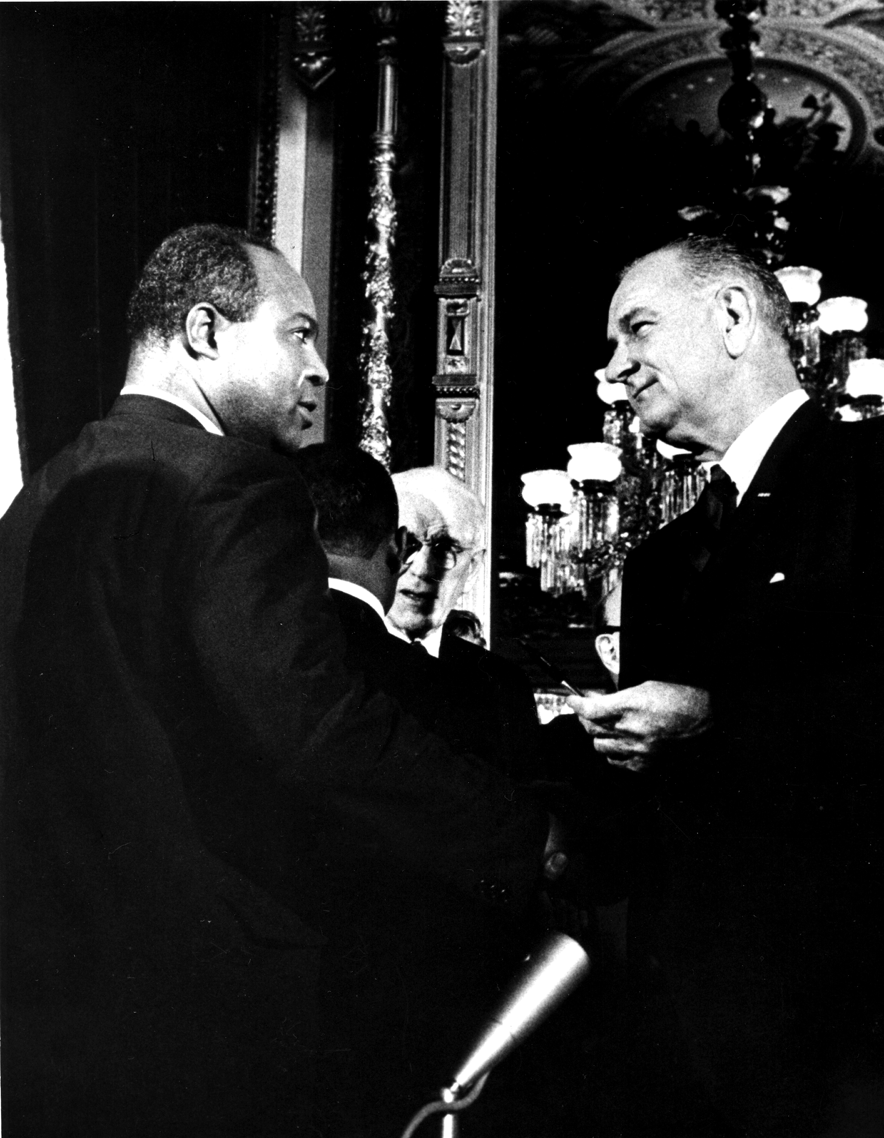 President Lyndon B. Johnson  presents one of the pens used to sign the Voting Rights Act of 1965 to the director of the Congress of Racial Equality (CORE) James L. Farmer Jr, Washington DC, August 6, 1965.