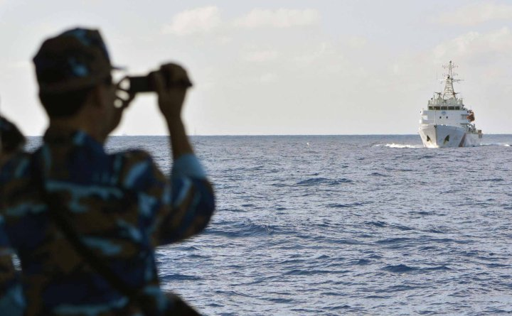 South China Sea, a crew member of a Vietnamese coast-guard vessel monitors the movements of a Chinese patrol ship