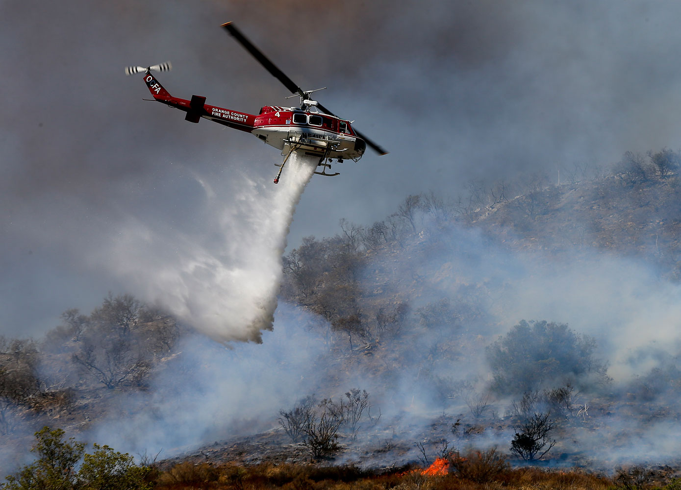 More than 280 firefighters are aided by water dropping helicopters and fixed-wing aircraft as they battle a 1,300-acre fire in Silverado Canyon, Calif., on Sept. 12, 2014.
