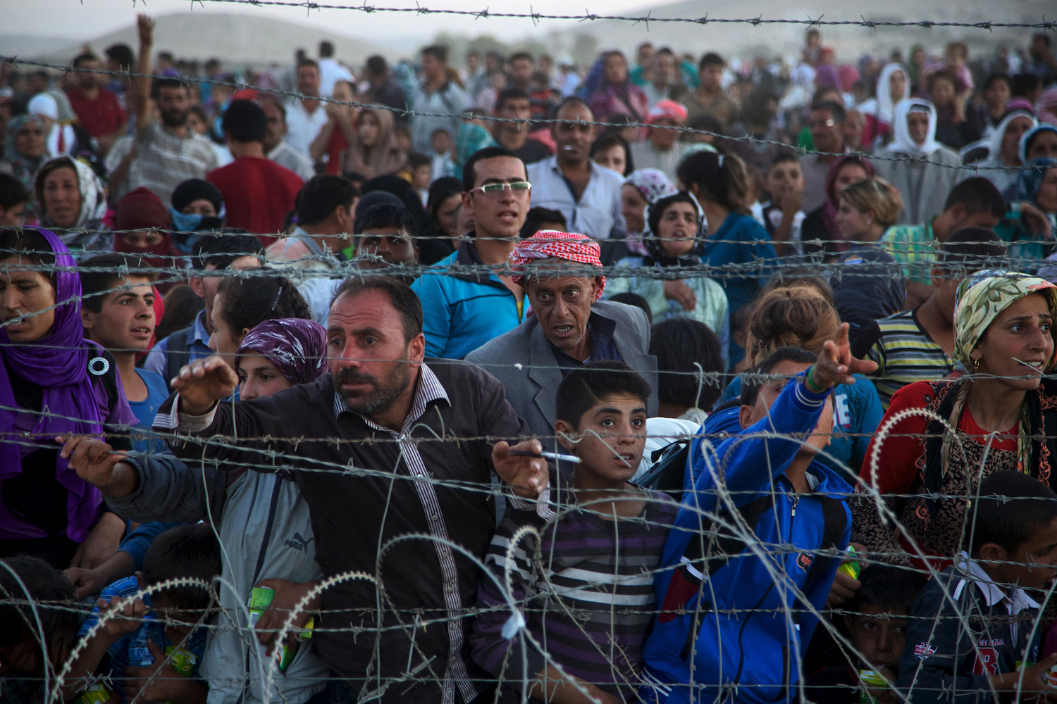 Up to 5,000 Syrians from Kobani amass at the border with Turkey on Friday evening, next to the Turkish village of Dikmetas.