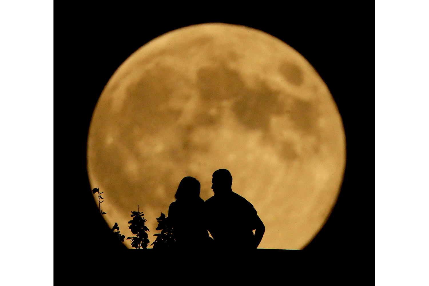 A couple sits on a bluff overlooking the Missouri River as the full moon rises in the distance Monday, Sept. 8, 2014, in Kansas City, Mo.