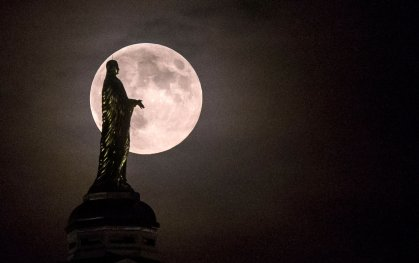 The harvest supermoon silhouettes the statue of the Virgin Mary on top the University of Notre Dame's golden dome in South Bend, Ind., on Sept. 8, 2014.