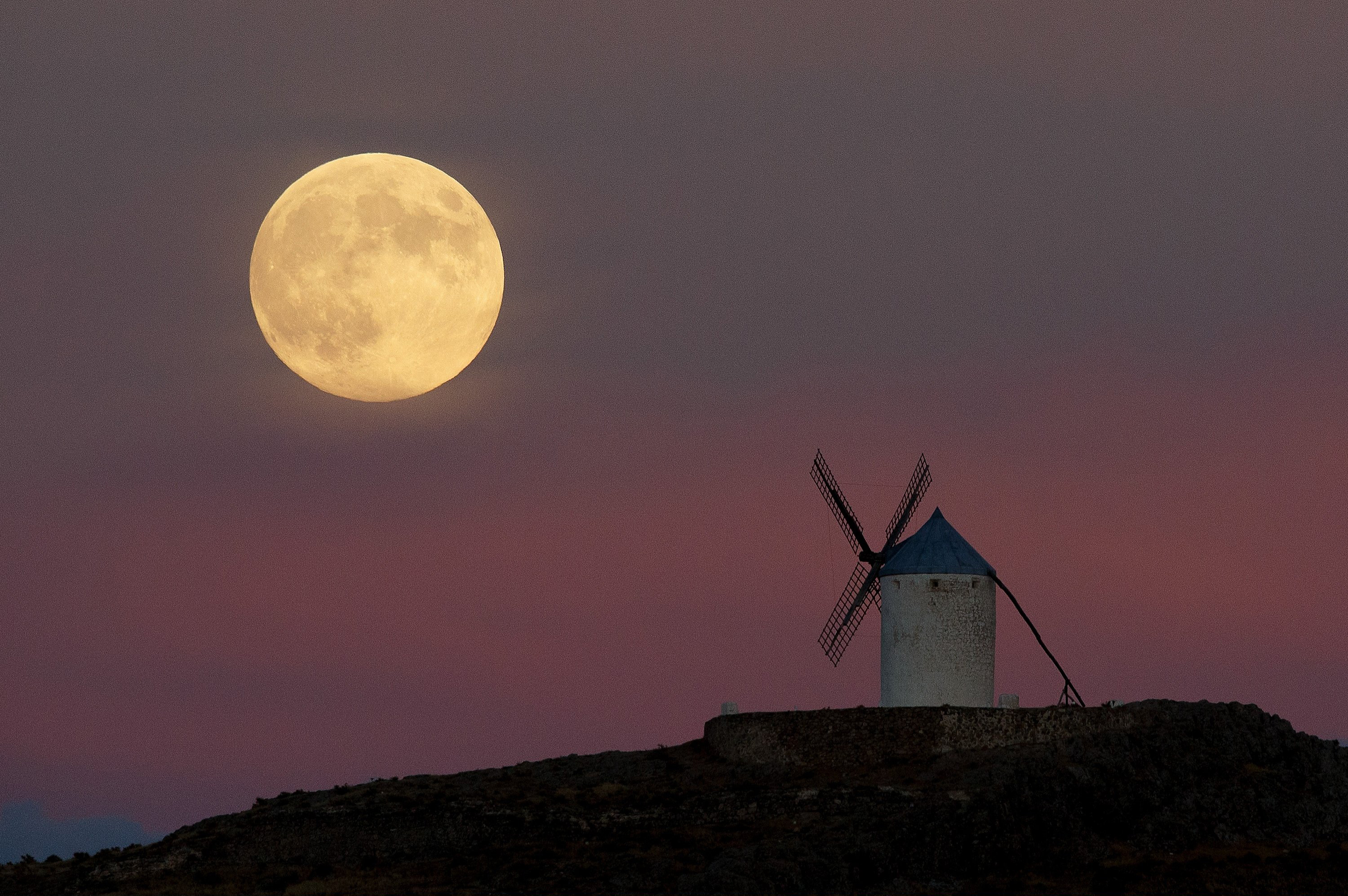 A moon appears behind a windmill a day before the supermoon is full on Sept. 8, 2014 in Consuegra, Toledo province, Spain.