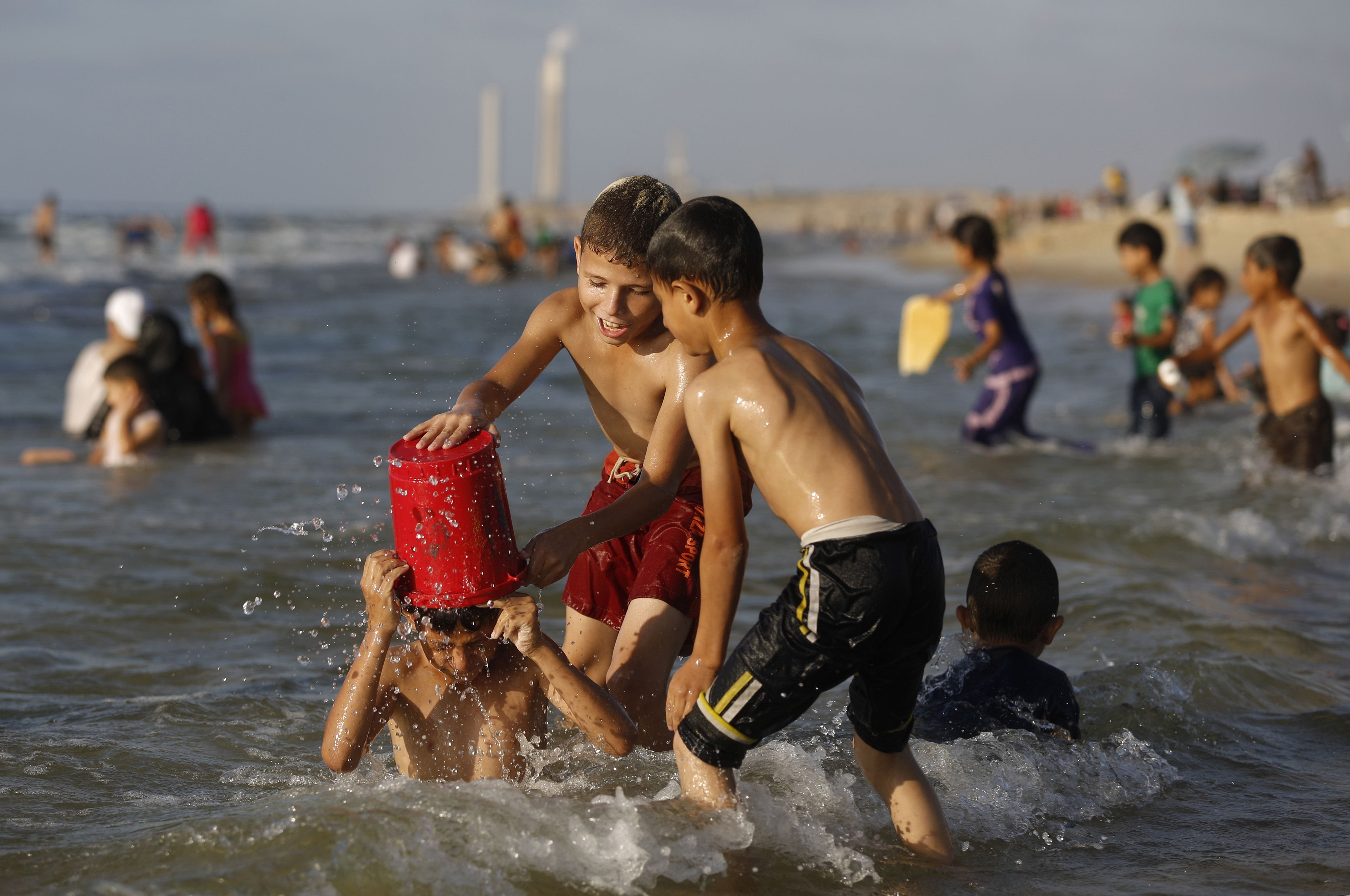 Palestinian children dump water on a boy as they swim on a beach, close to the divide with Israel, near Gaza City on Sept. 12, 2014.